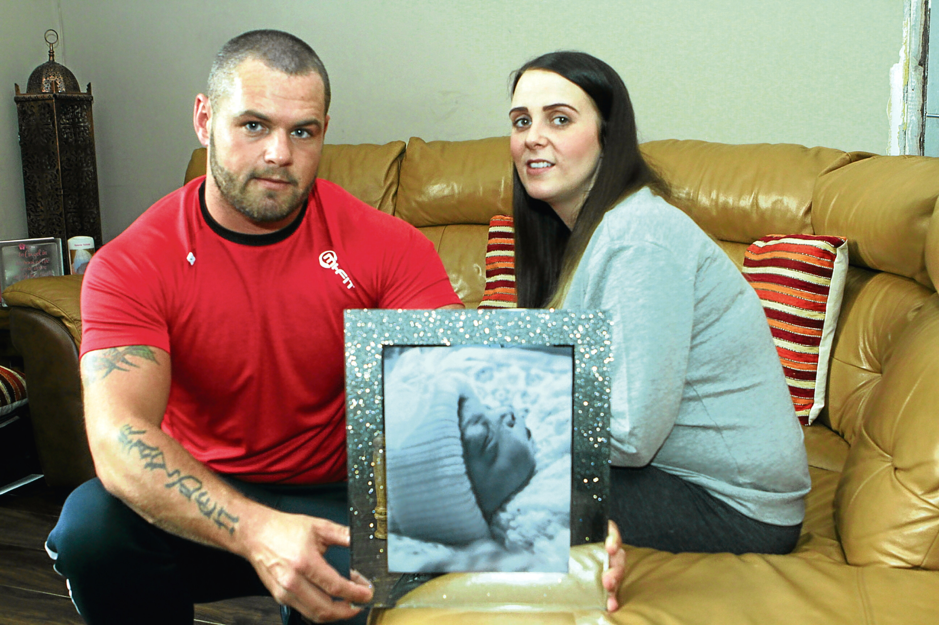 Brian Tolmie and Robyn Stevens with a photograph of their daughter Konnie, who was stillborn.