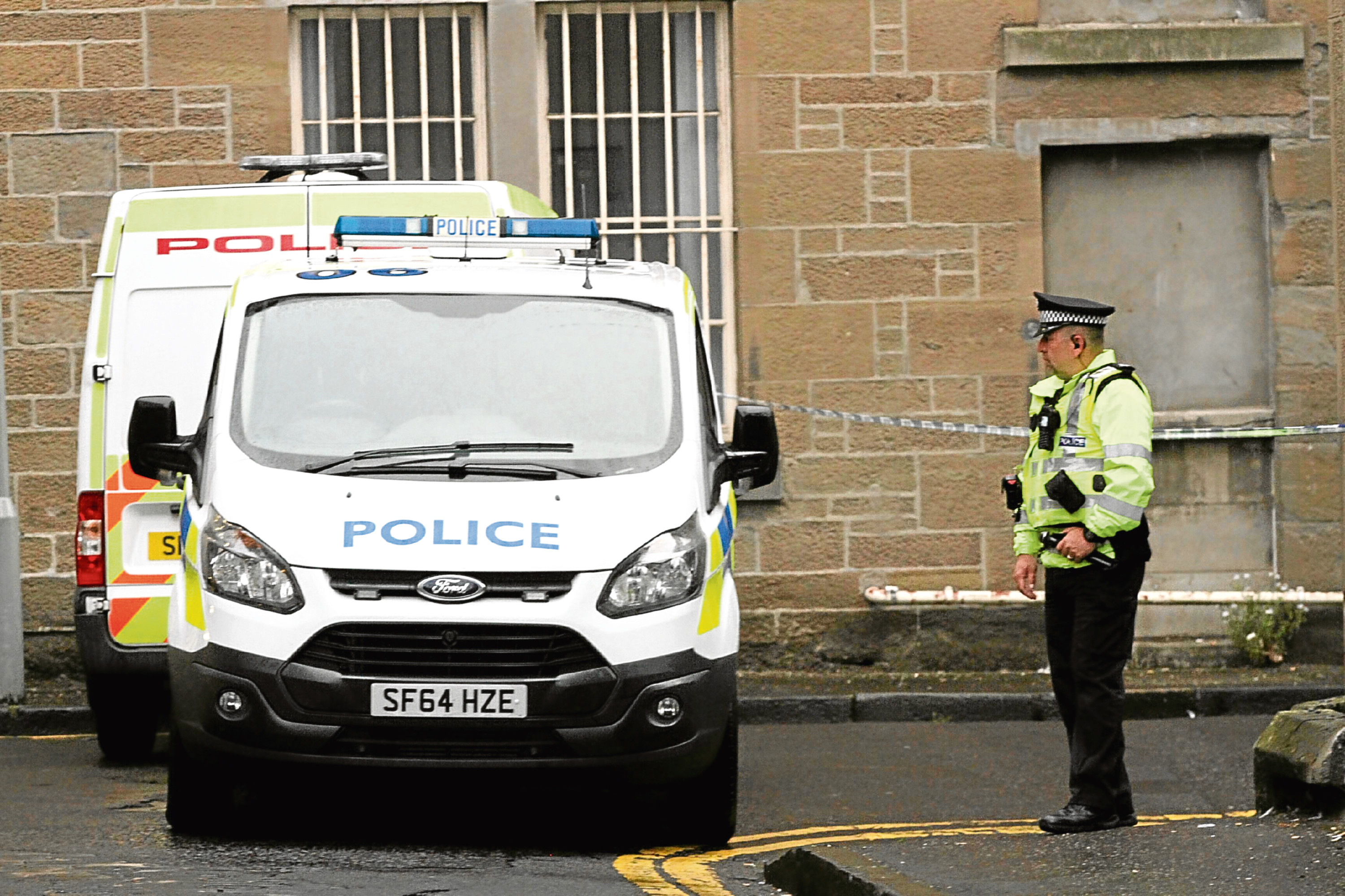 Police vehicles and an officer in Forester Street close to where Steven Smeaton was found.