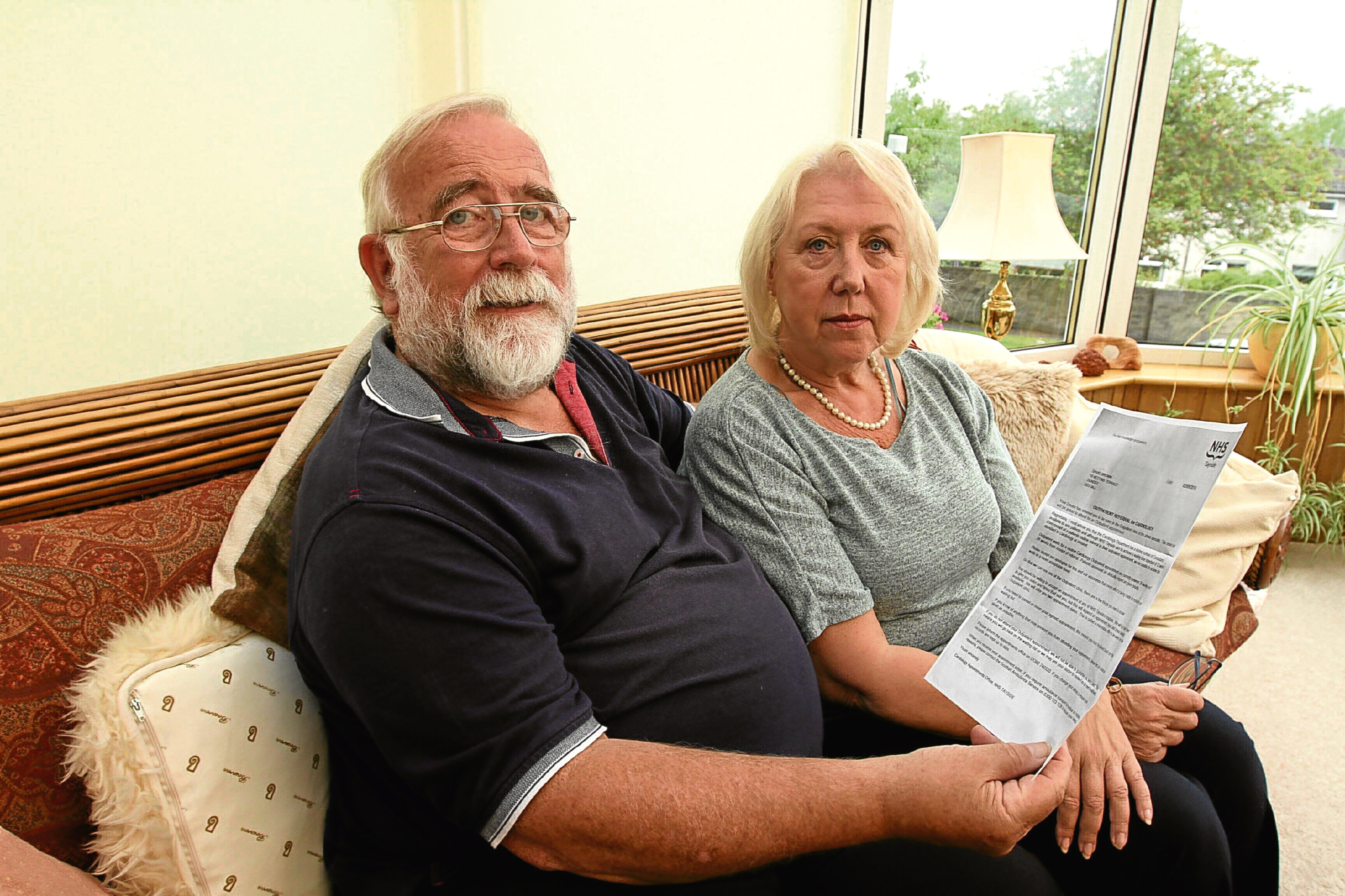 David and his wife Dorothy Brown at their Dundee home with the letter from NHS Tayside.