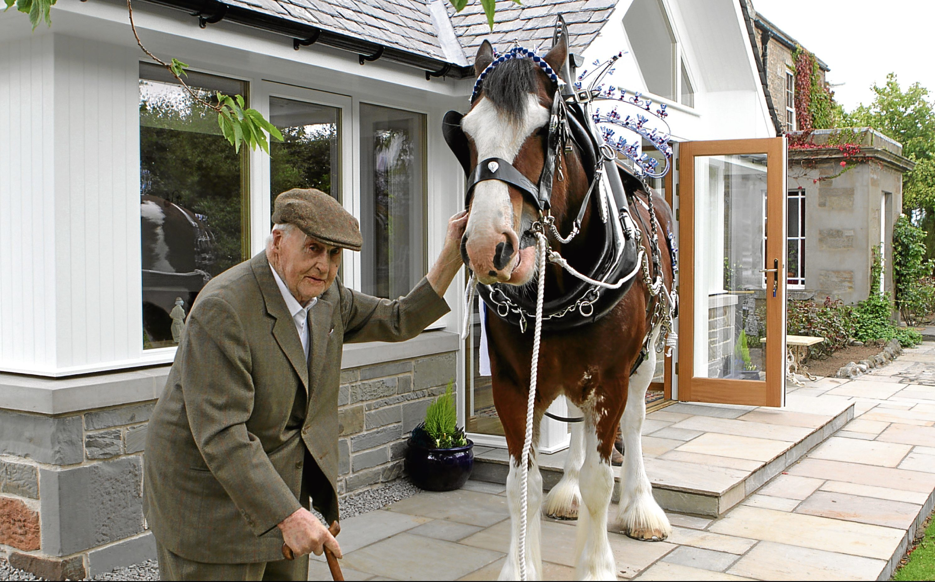 John meets Geordie the Clydesdale at his home in Carnoustie during his 100th birthday celebrations.