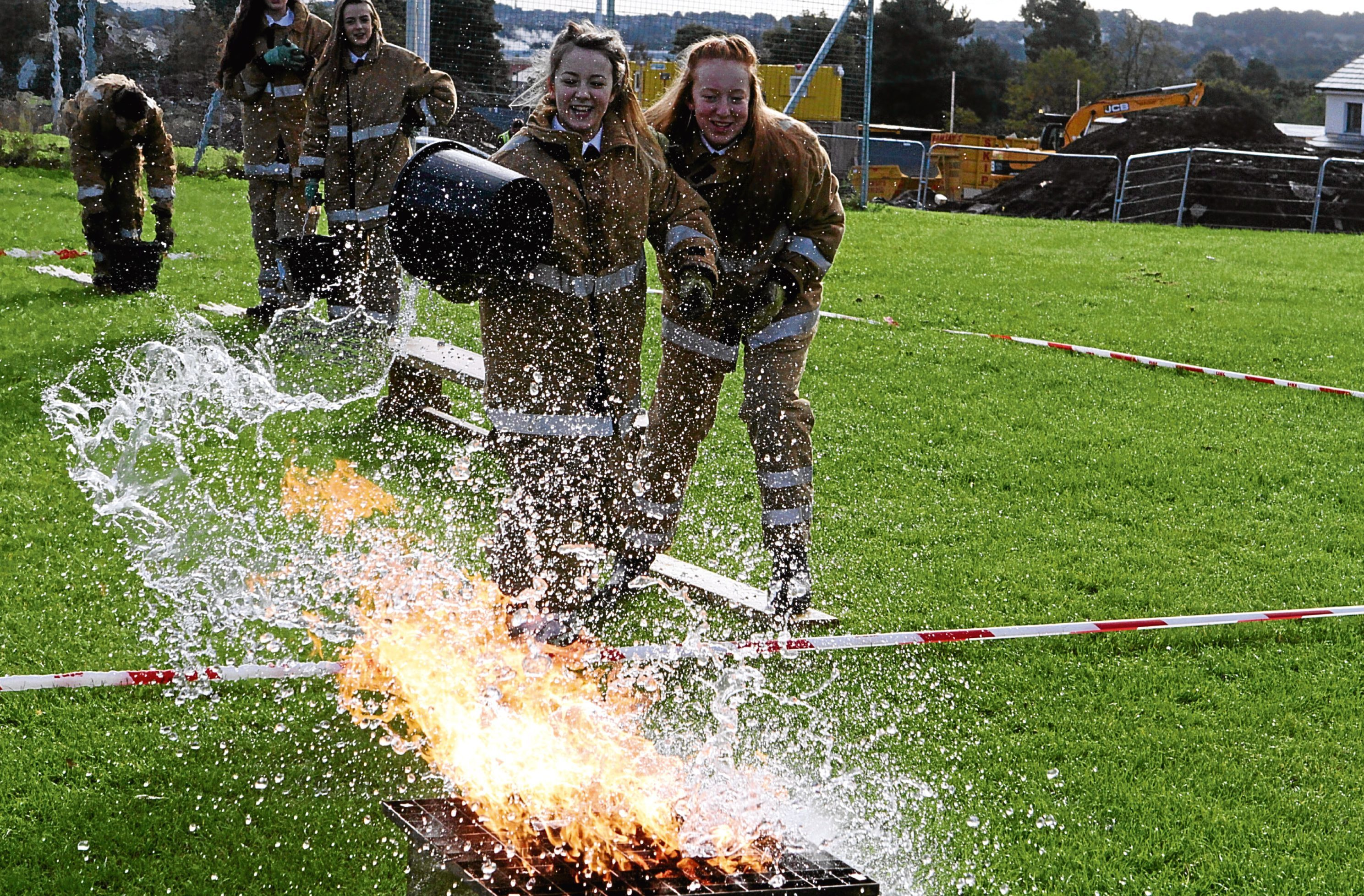 Picture shows pupils taking part in a fire-fighting exercise.