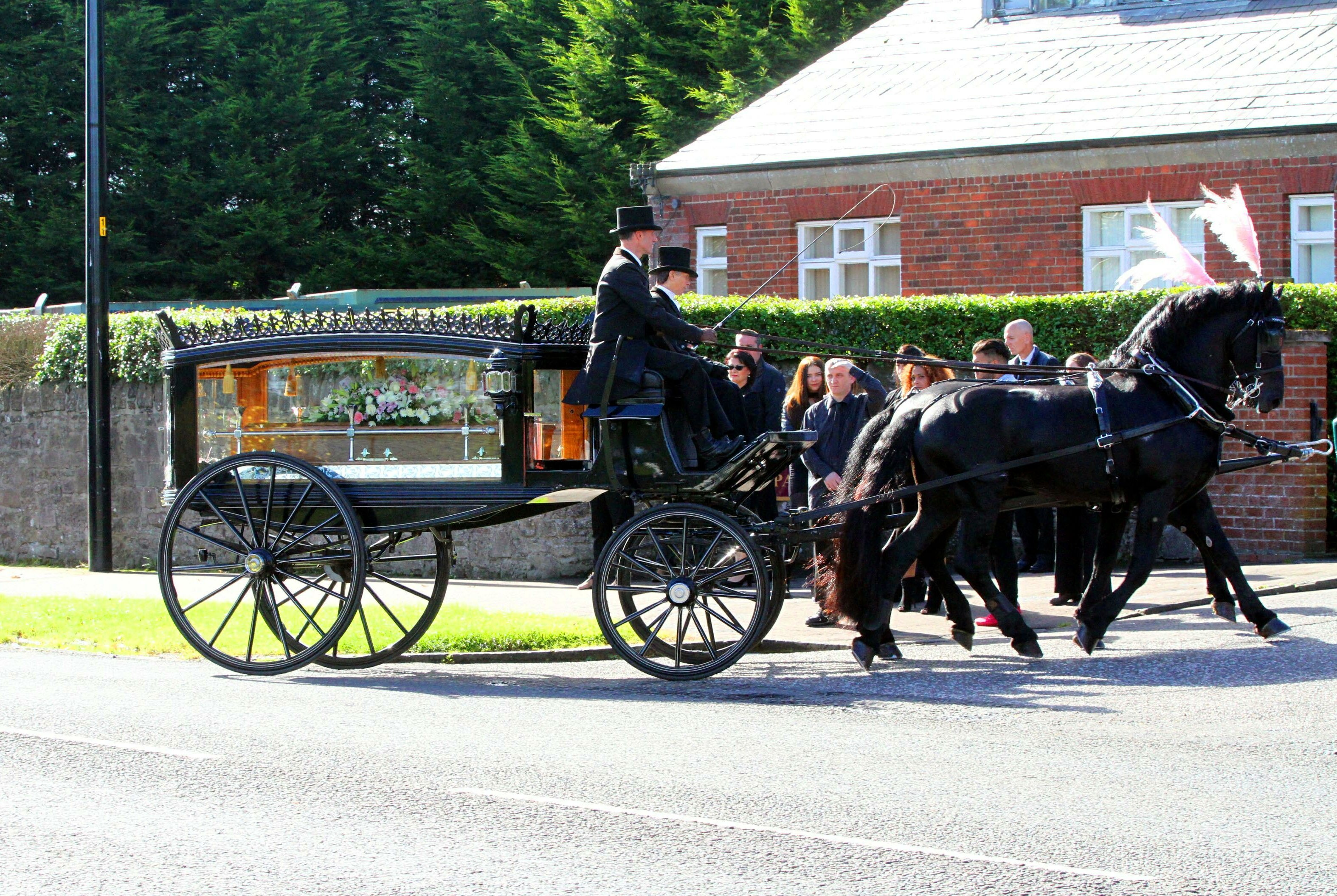 Marie's coffin enters the grounds of the crematorium.