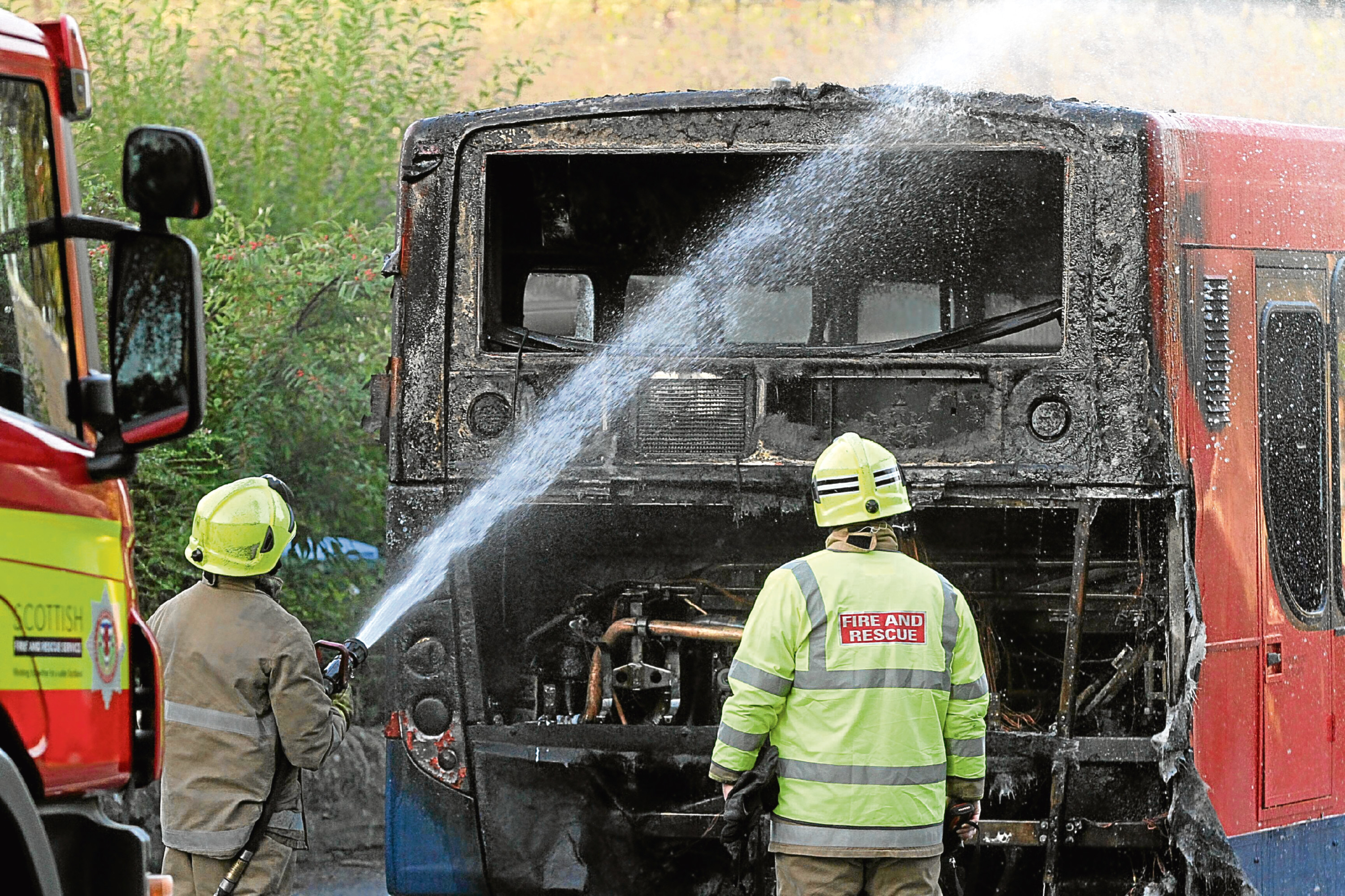 Firefighters see to the damaged bus