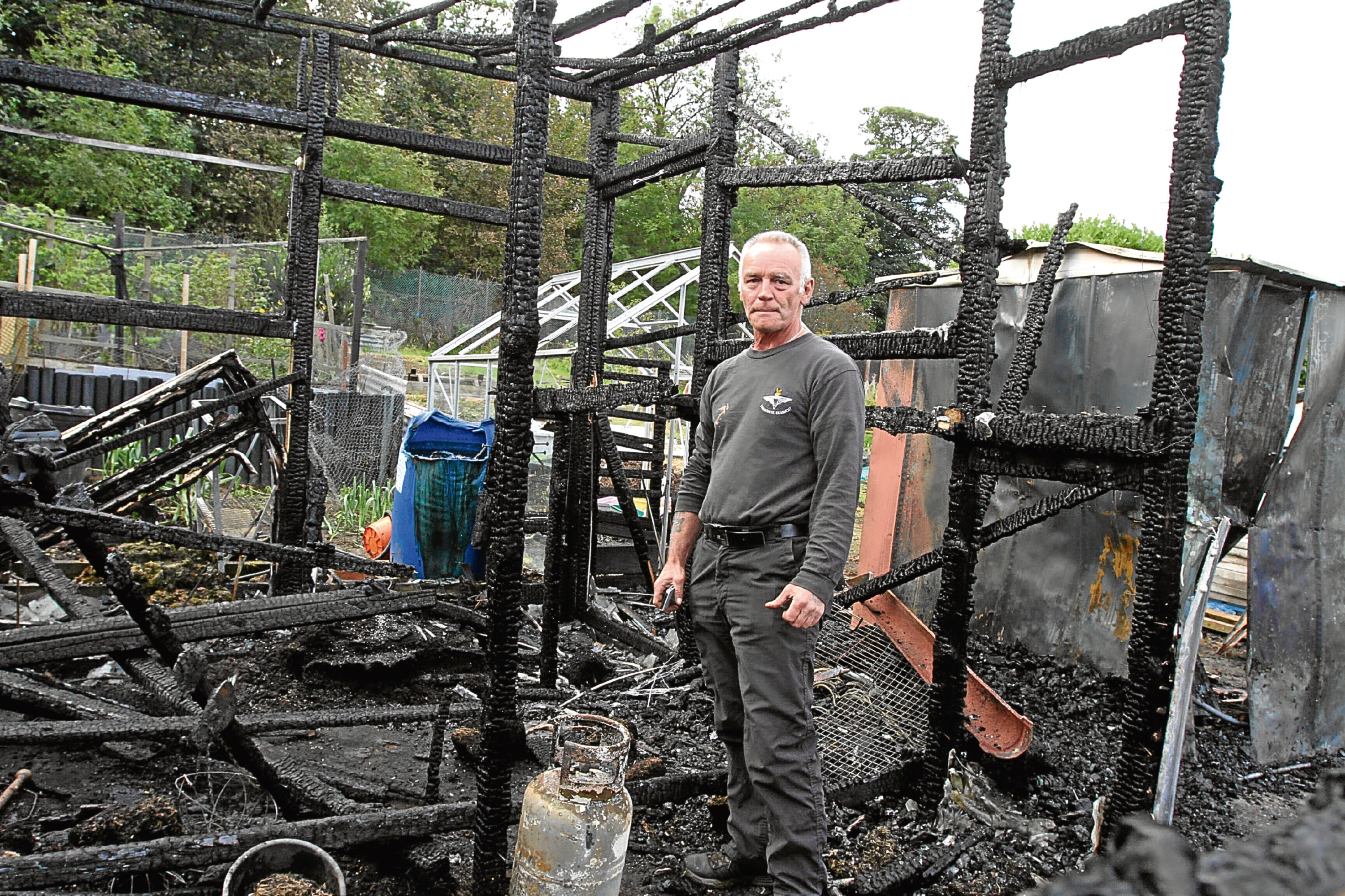 Kenny Watts beside his burnt-out greenhouse.