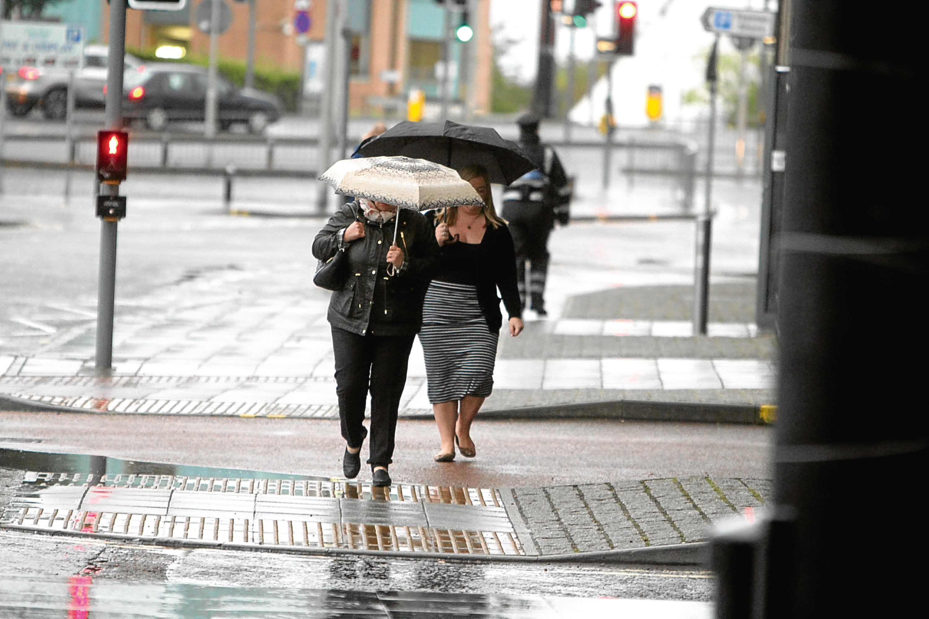 Folk in the city centre take shelter from yesterday's wet weather.