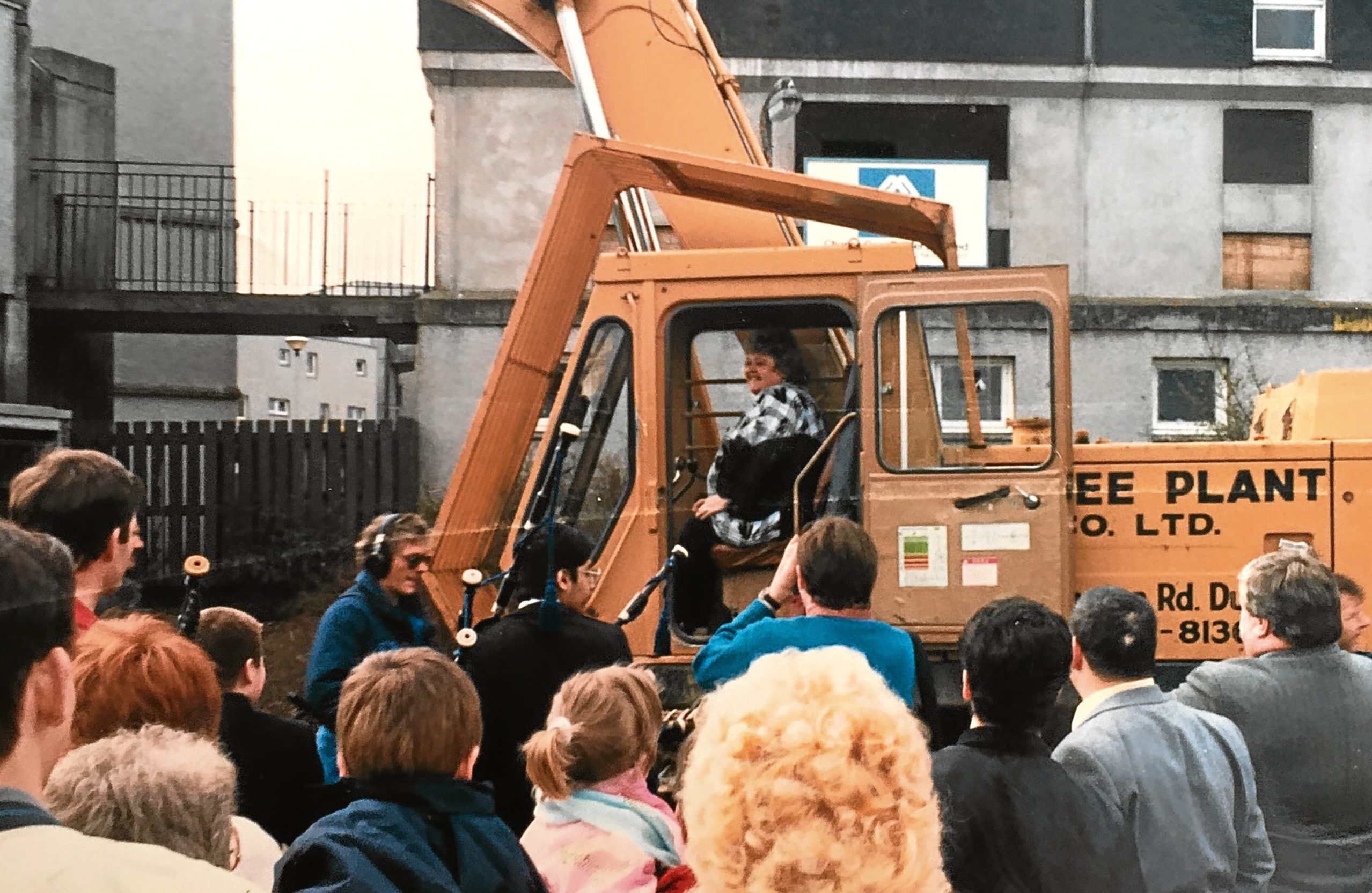 Jane driving a digger during the demolition of flats.