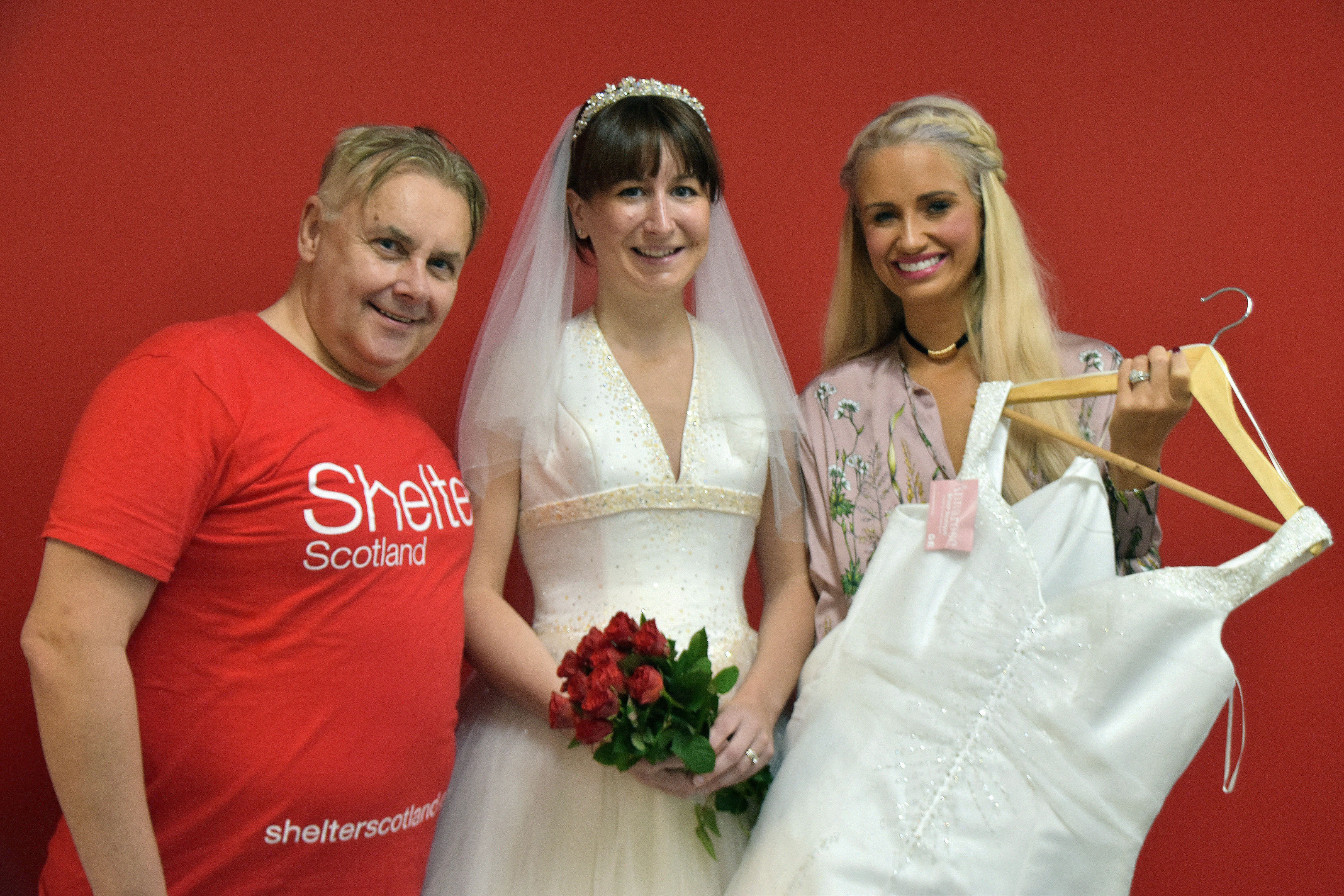 John Sinclair of Shelter, Carolyn Smart and Anne Elder with two of the wedding dresses which have been donated.