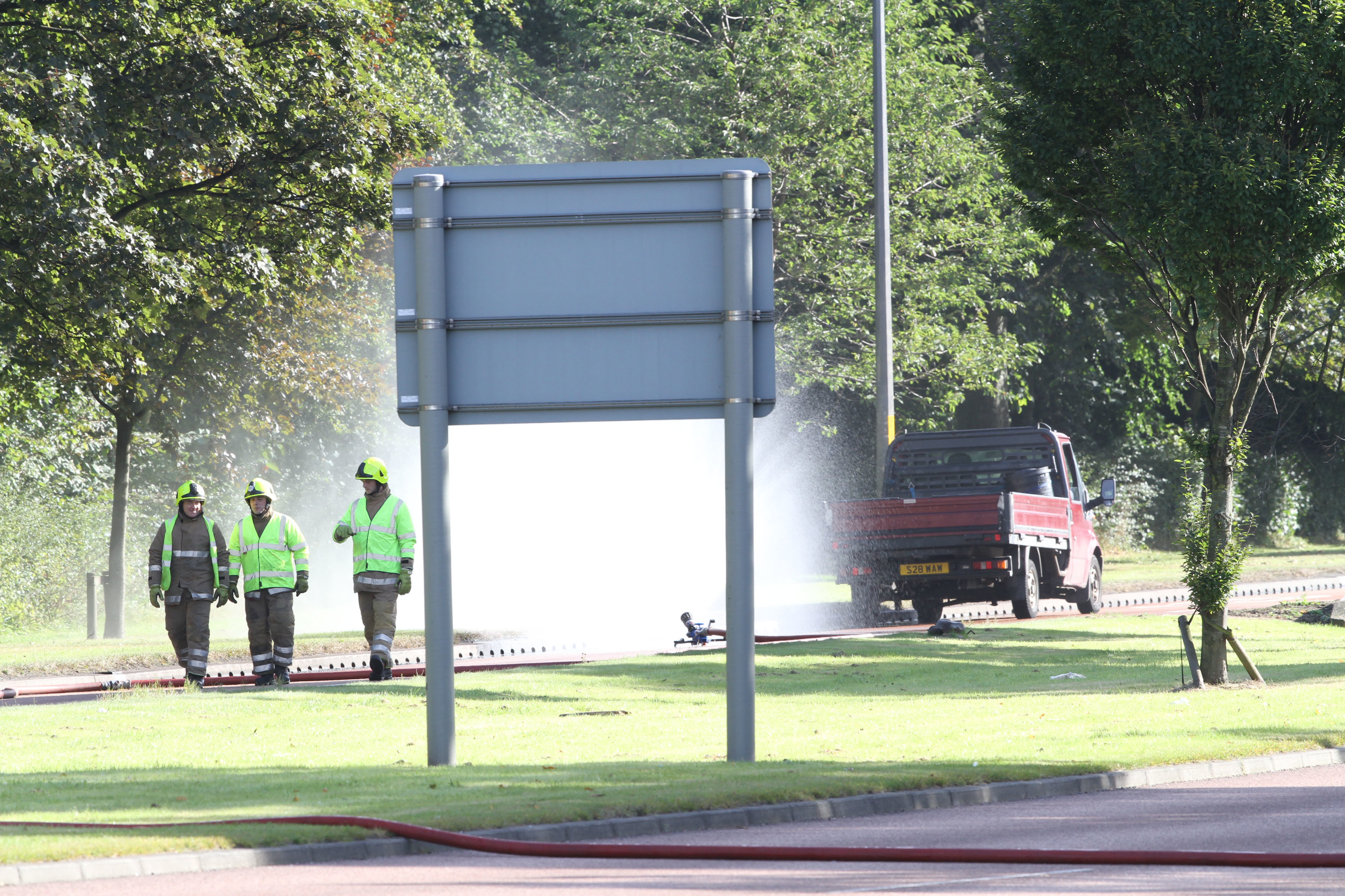 The scene of the incident. Firefighters used a hose to spray the leaking cylinder.