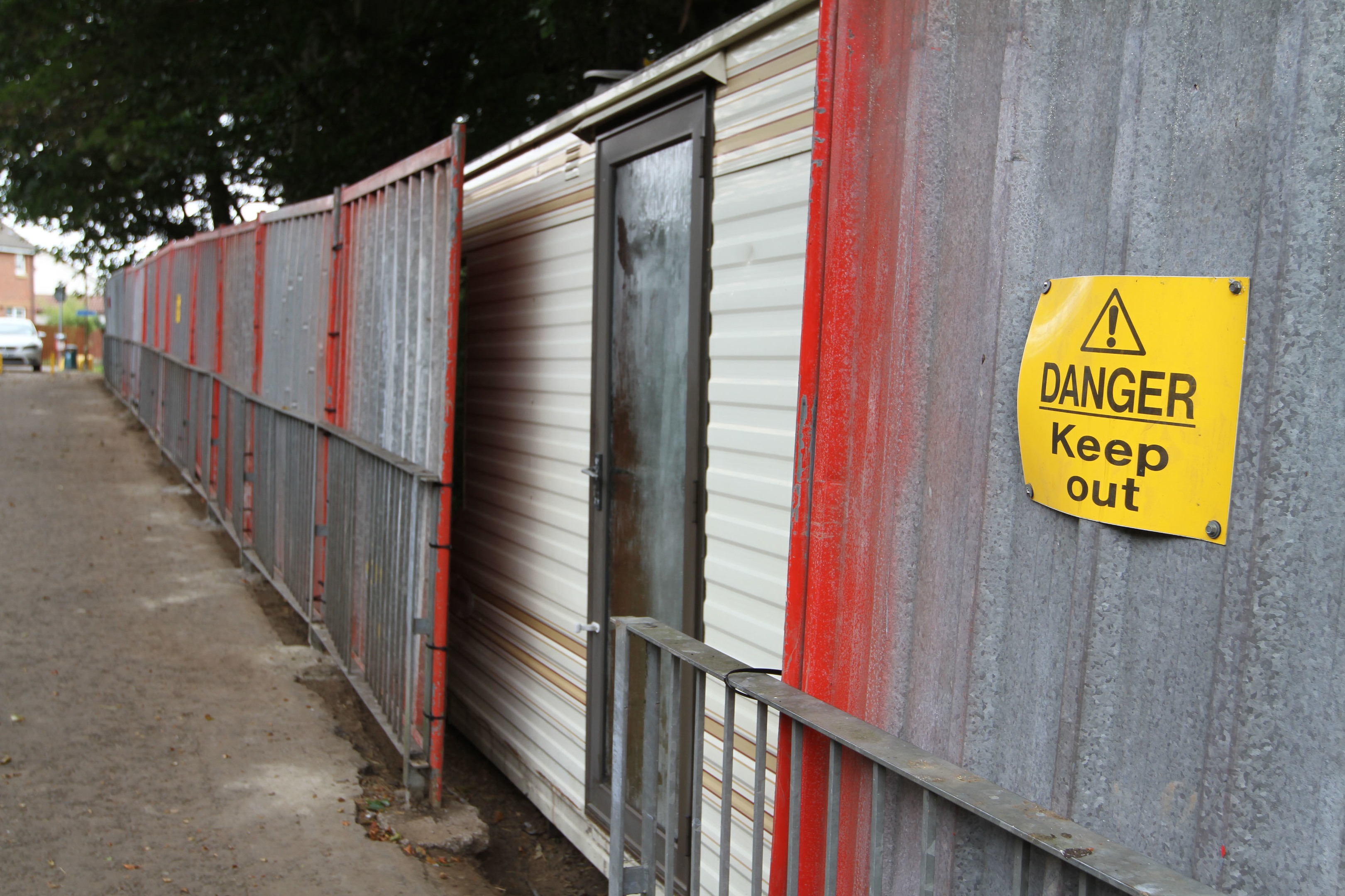 "Corrugated metal fencing, complete with ""danger, keep out"" signs, has been erected around the caravan."