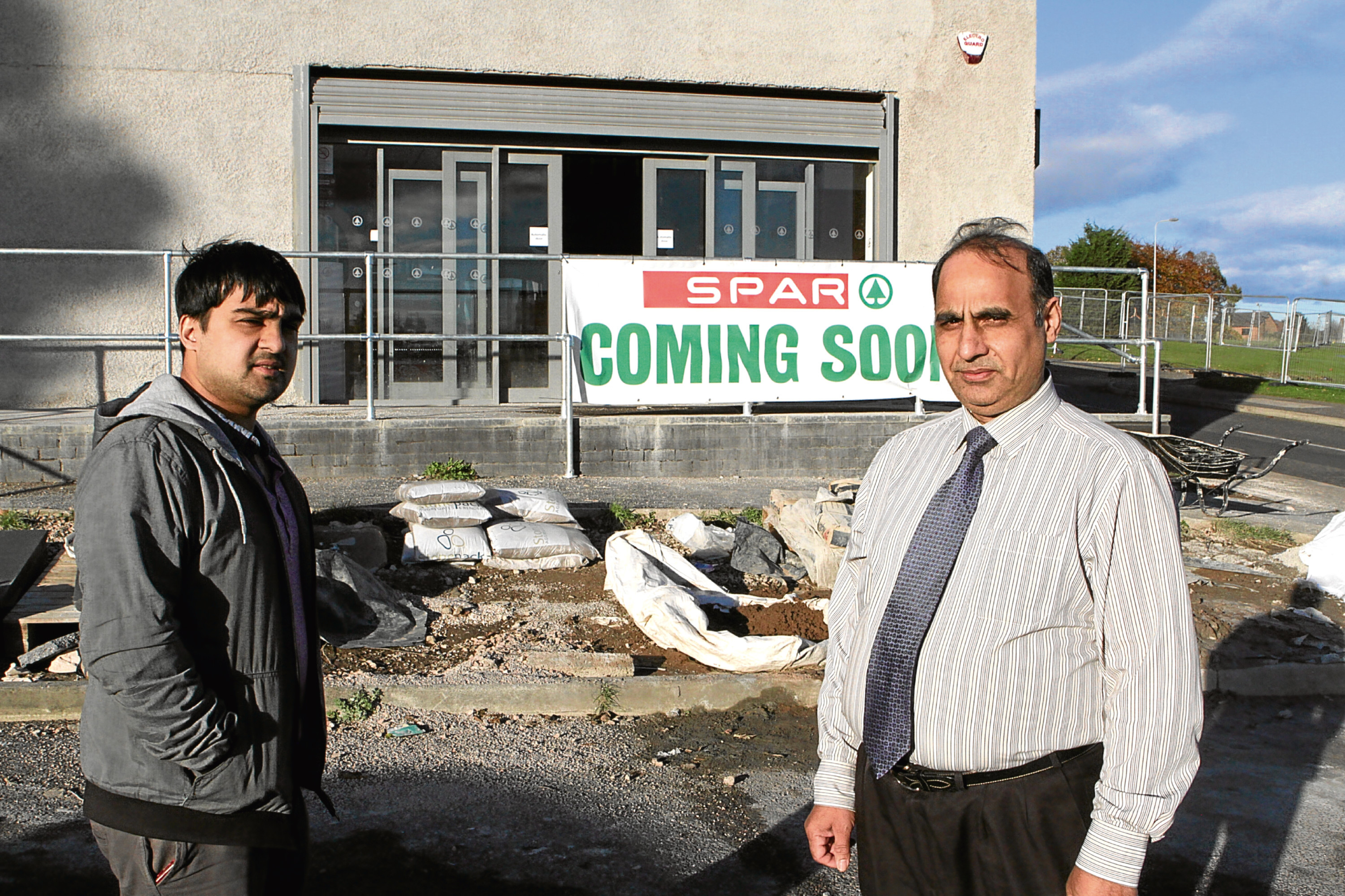 Saeed and Mohammed Asif outside the Spar store, which has been hit by flooding.