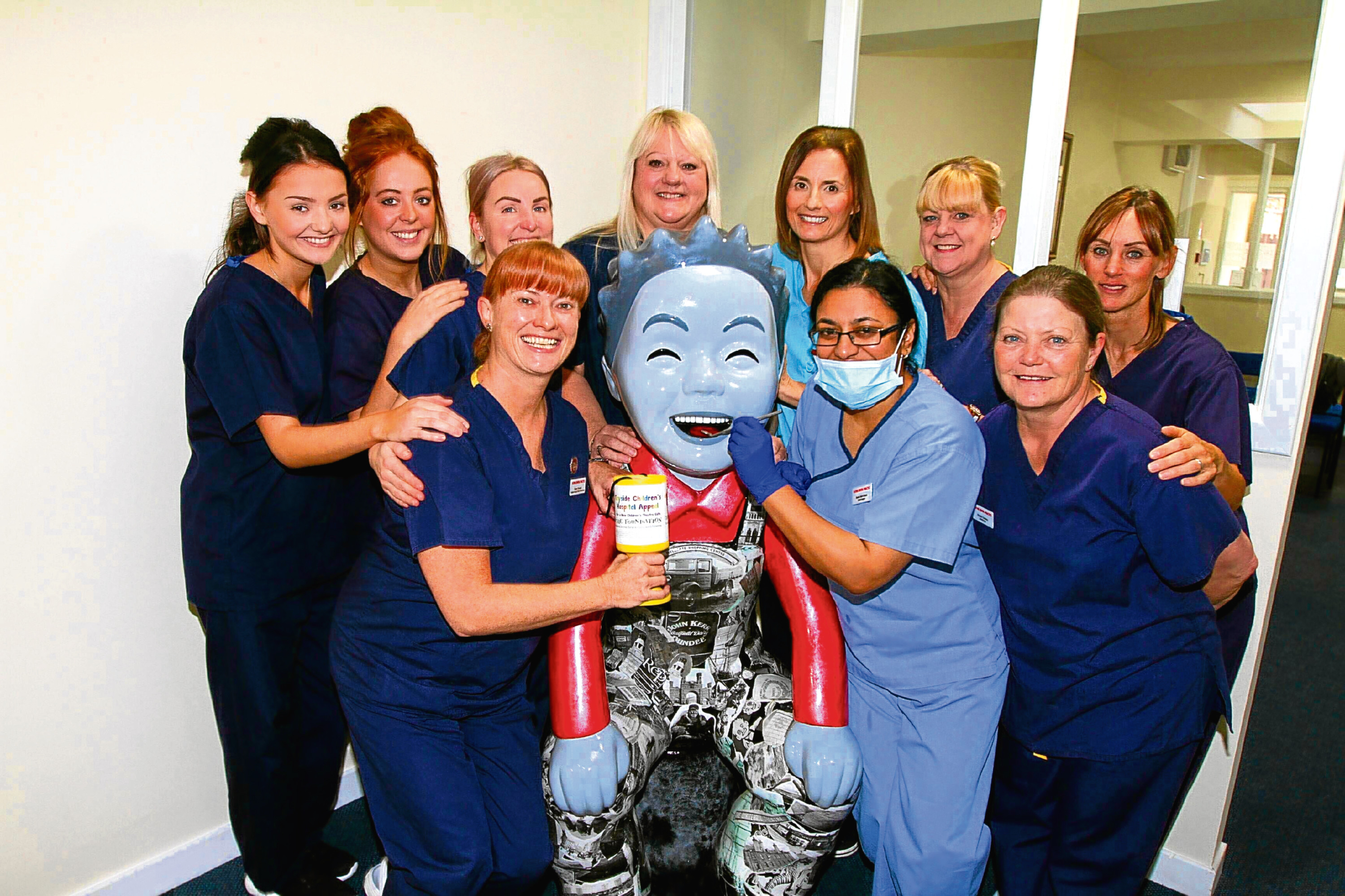 Past and Present Oor Wullie at Duthie Dental Practice along with staff members.