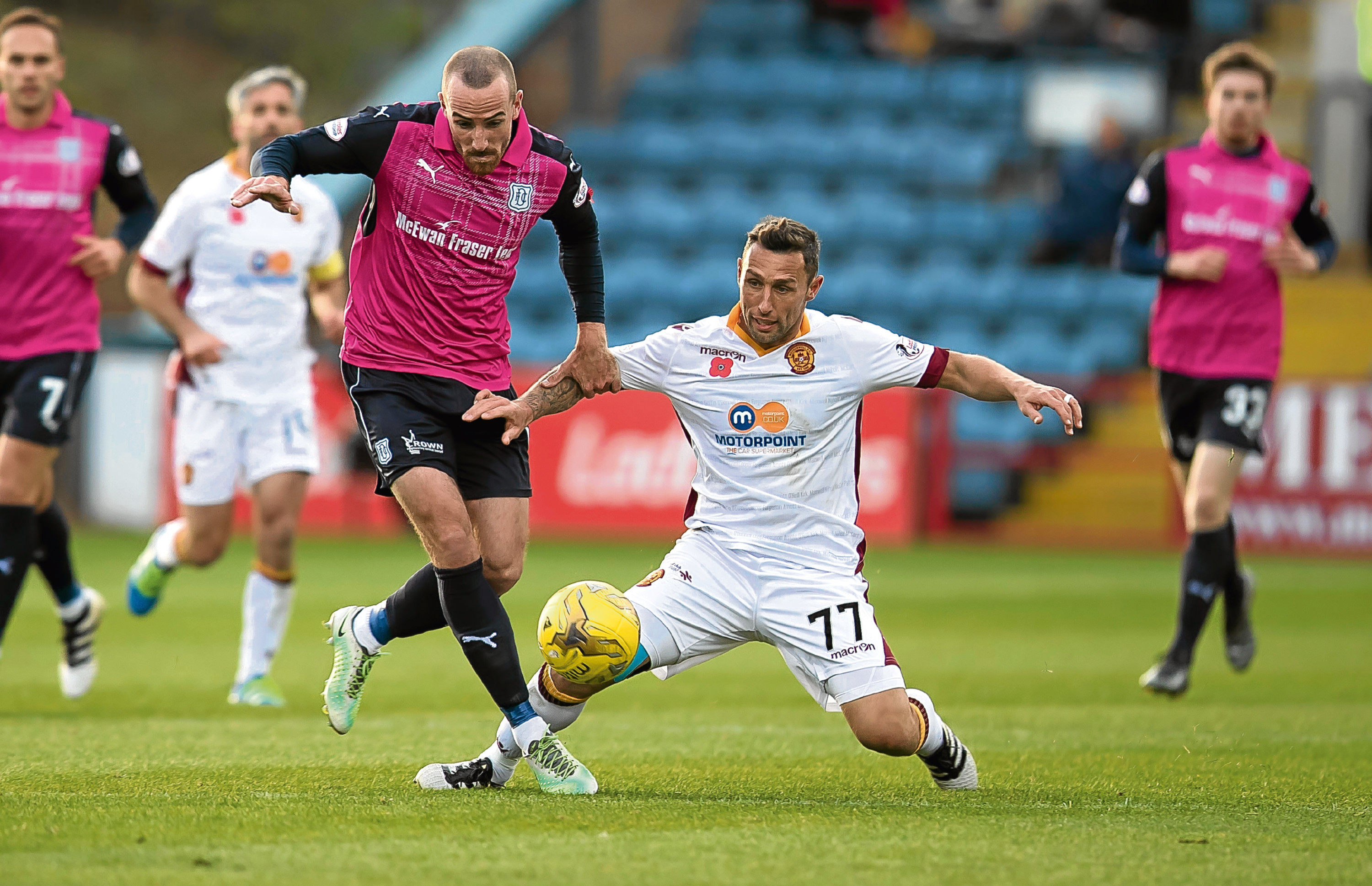 Dundee midfielder James Vincent rides the challenge from Motherwell's Scott McDonald in Saturday's 2-0 win at Dens.