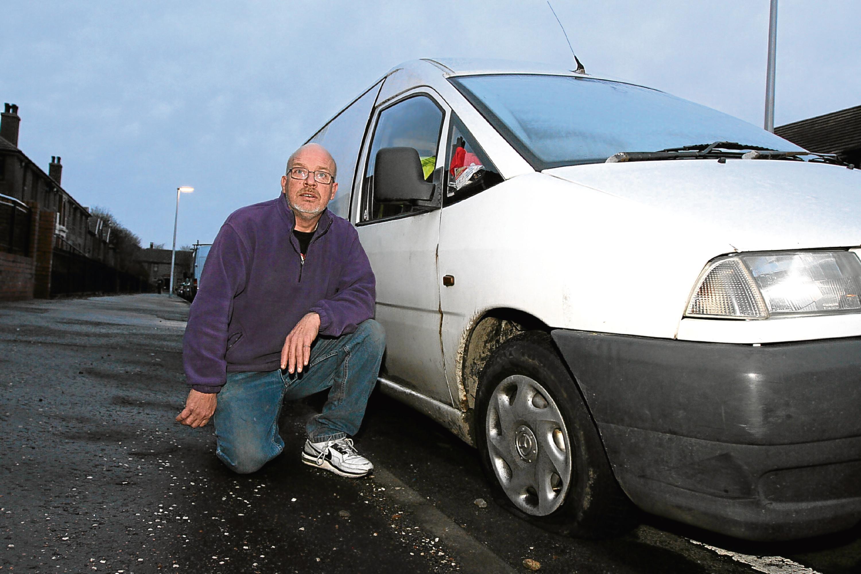 Tony McAteer beside his van, which was targeted in a tyre-slashing spree