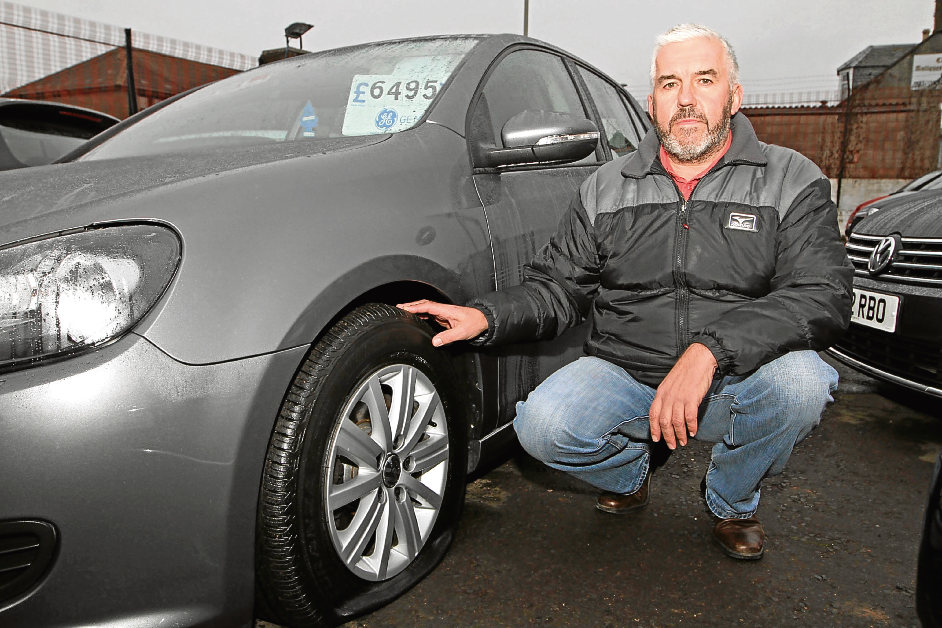 Gordon Sinclair next to one of the vehicles damaged at Cowgate Motors.