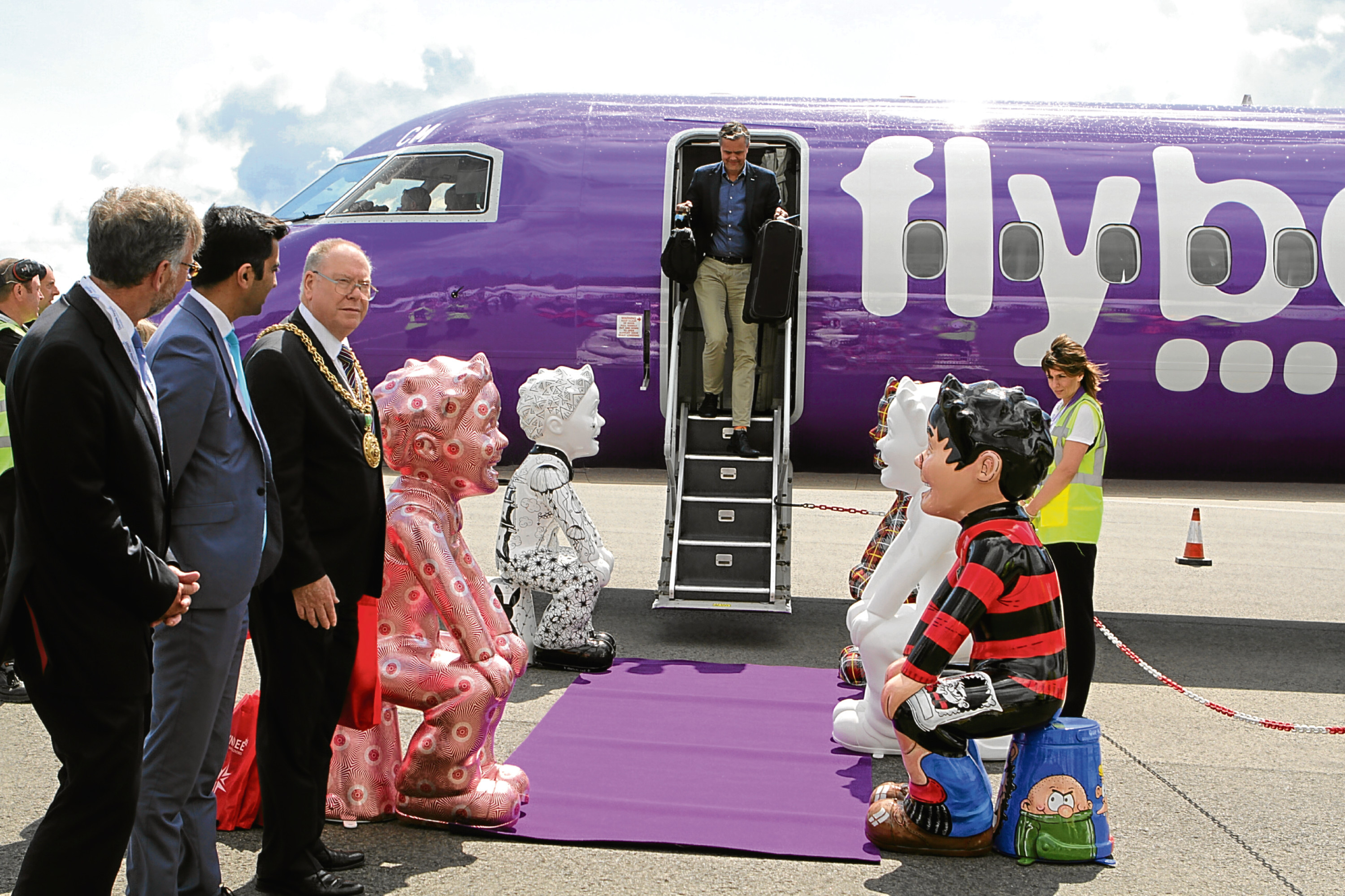 Dignitaries and statues from the Oor Wullie Bucket Trail welcome the first passenger from Amsterdam back in May.
