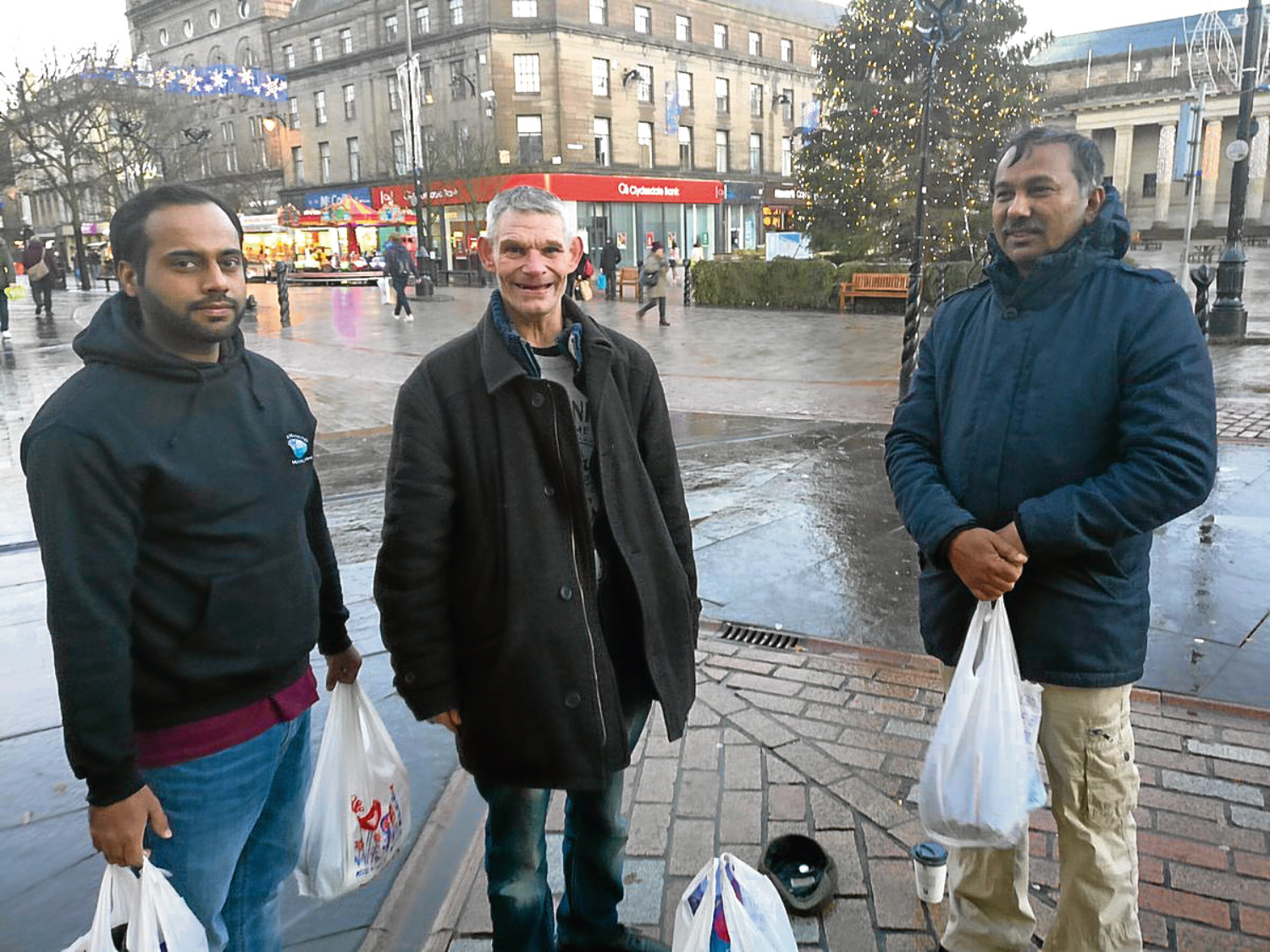 Naseh Ahmed (left) and Dr Golam Kabir, volunteers with the Dundee AMYA, speak to a member of the Dundee homeless community in the city centre.