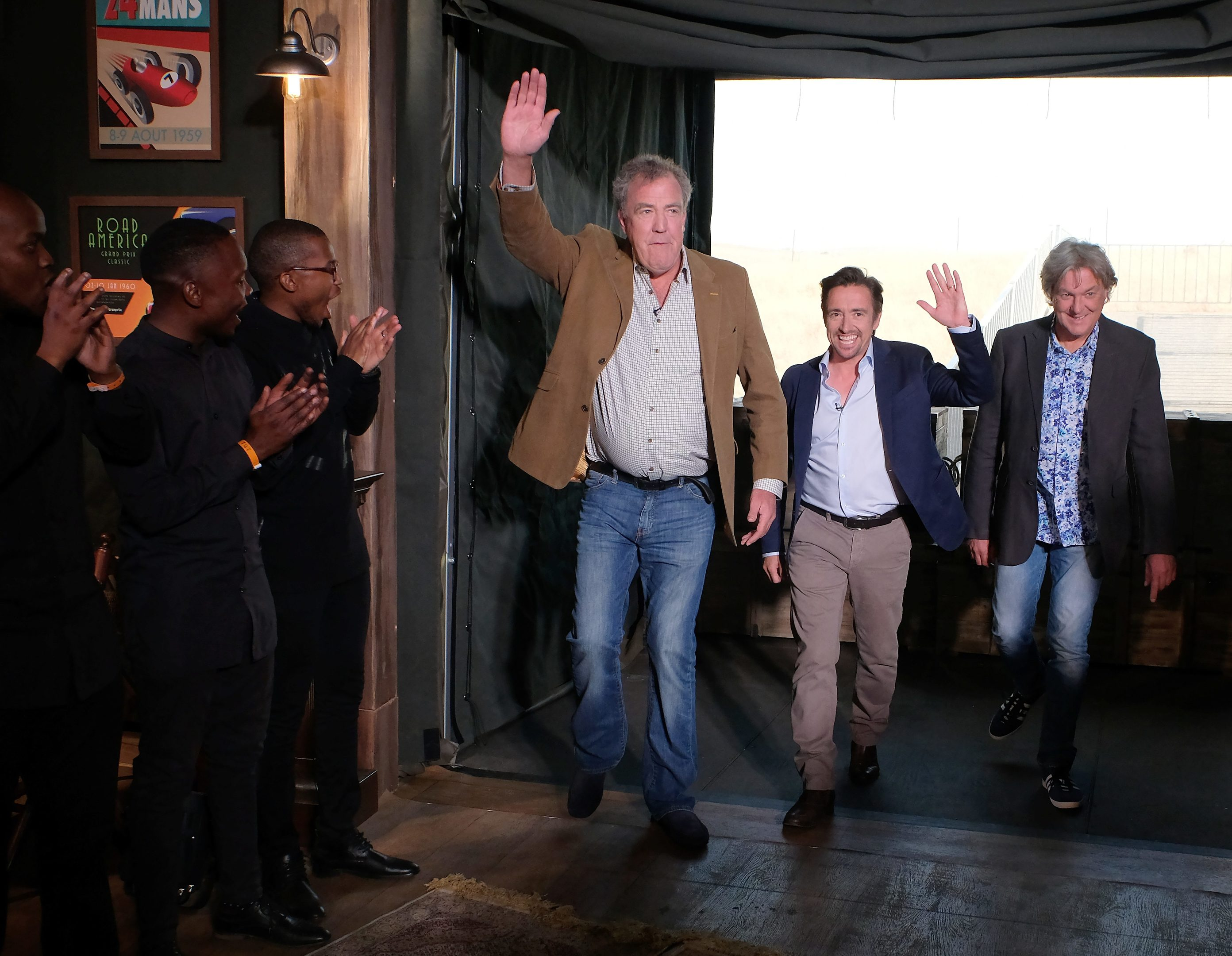 Jeremy Clarkson, Richard Hammond and James May enter The Grand Tour studio.