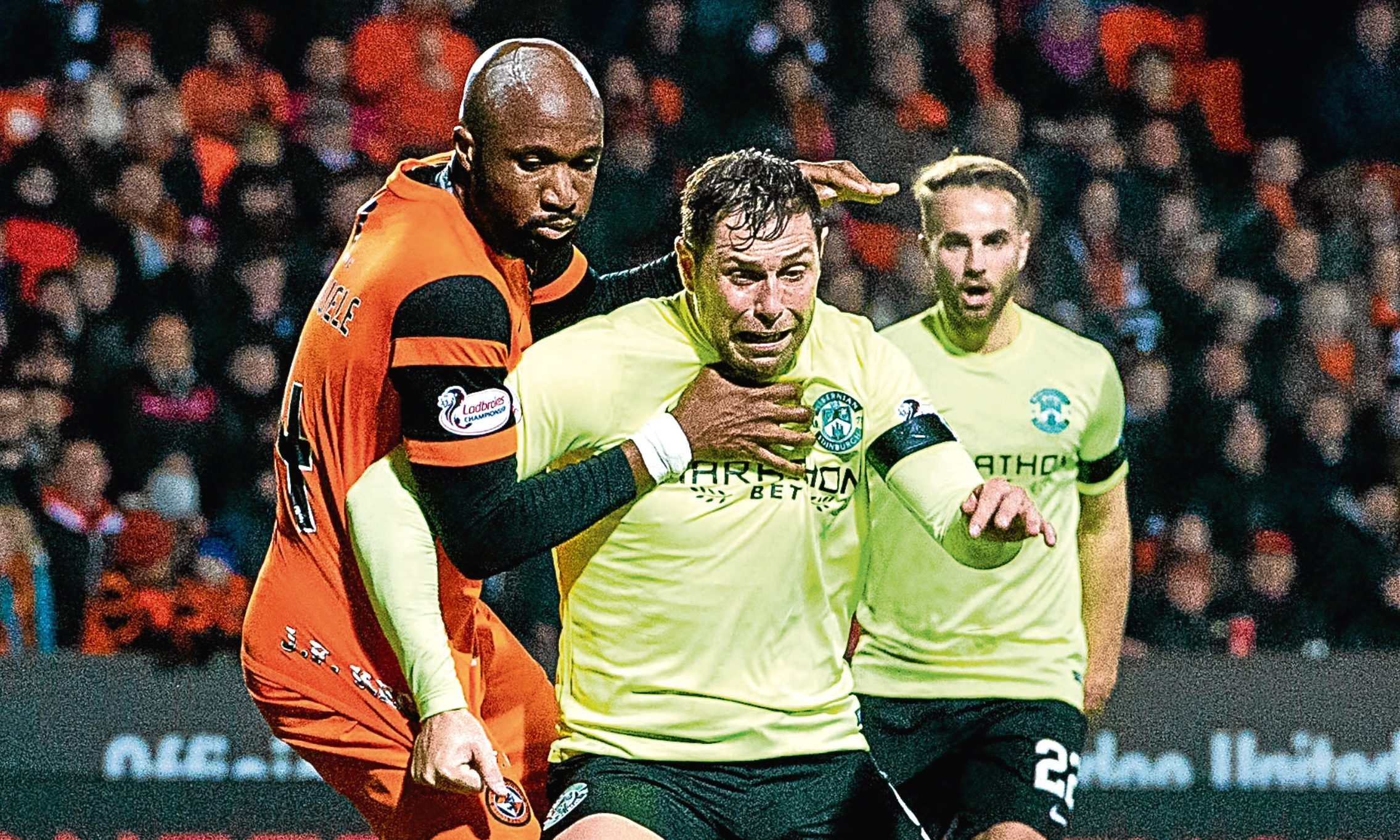 Dundee United defender William Edjenguele gets to grips with Hibs' Grant Holt the last time the two sides played