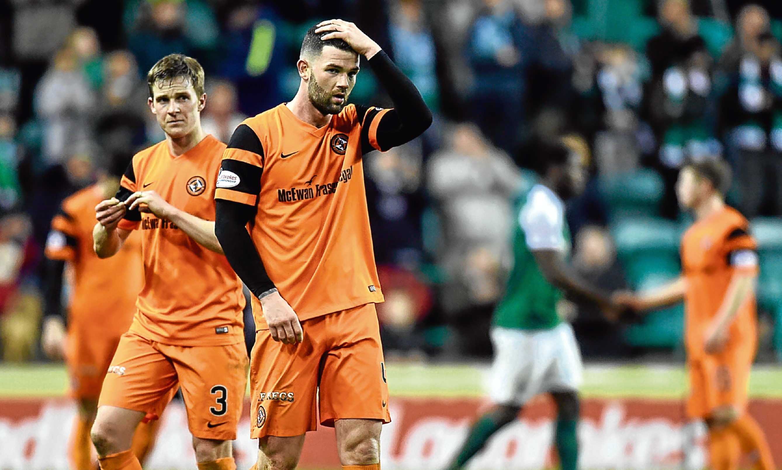 Dundee United defenders Mark Durnan and Paul Dixon trudge off at Easter Road.