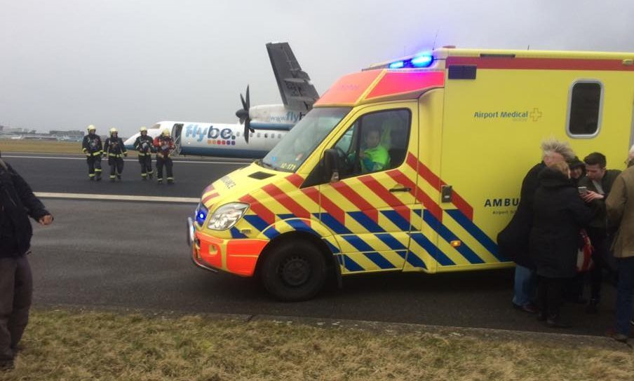 The crashed plane behind an ambulance on the runway