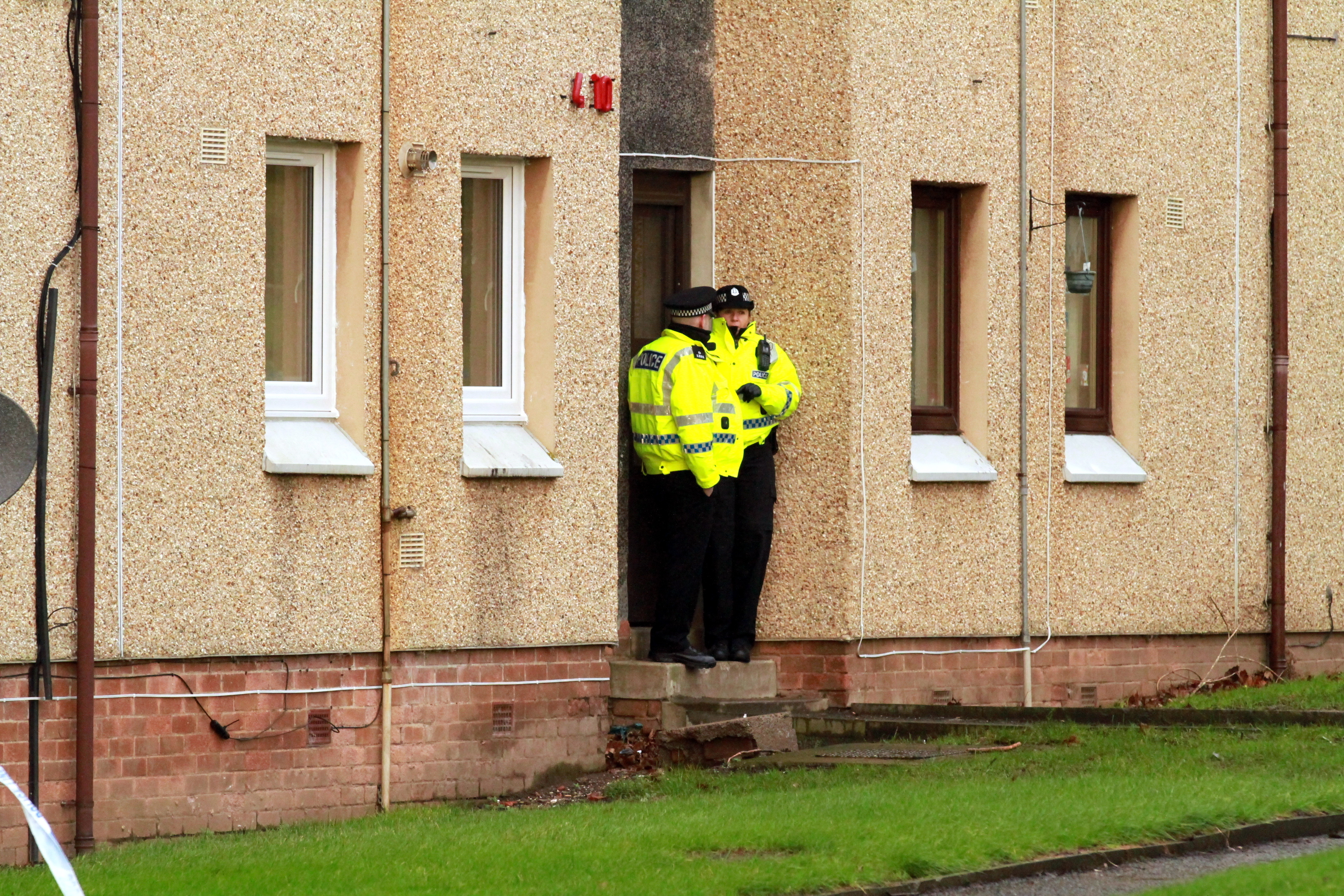Police guard the door of a block of flats on Thurso Crescent, where Aigars Upieneks' body was found.