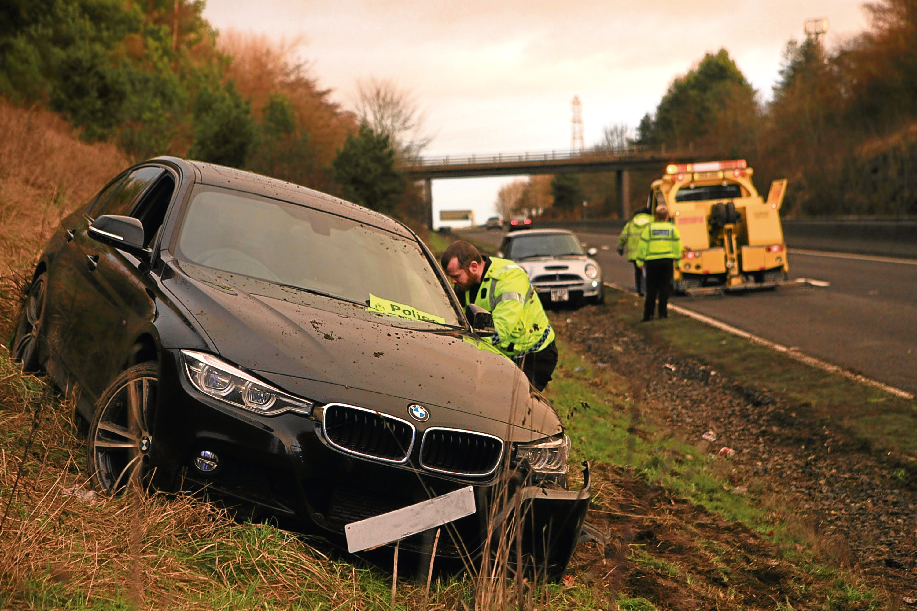 Police attending the scene of the two-car crash today, which left a black BMW on the embankment of the A90.