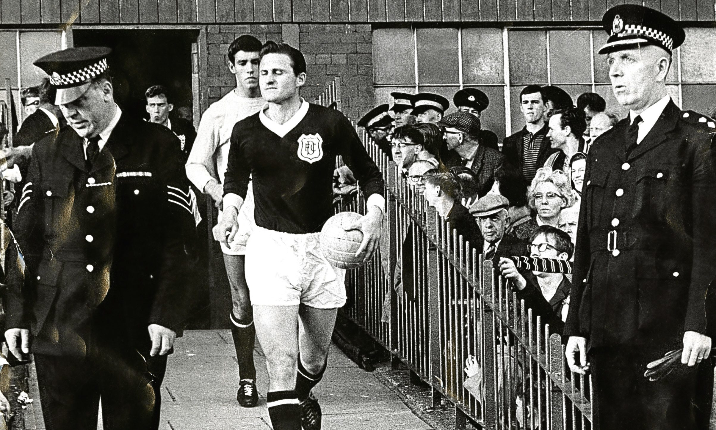 It's August 1965 and a rare foray as captain of Dundee, as Alan Cousin leads the team out at Dens Park, followed by goalkeeper Ally Donaldson. Good security on hand, too, from the local constabulary.
