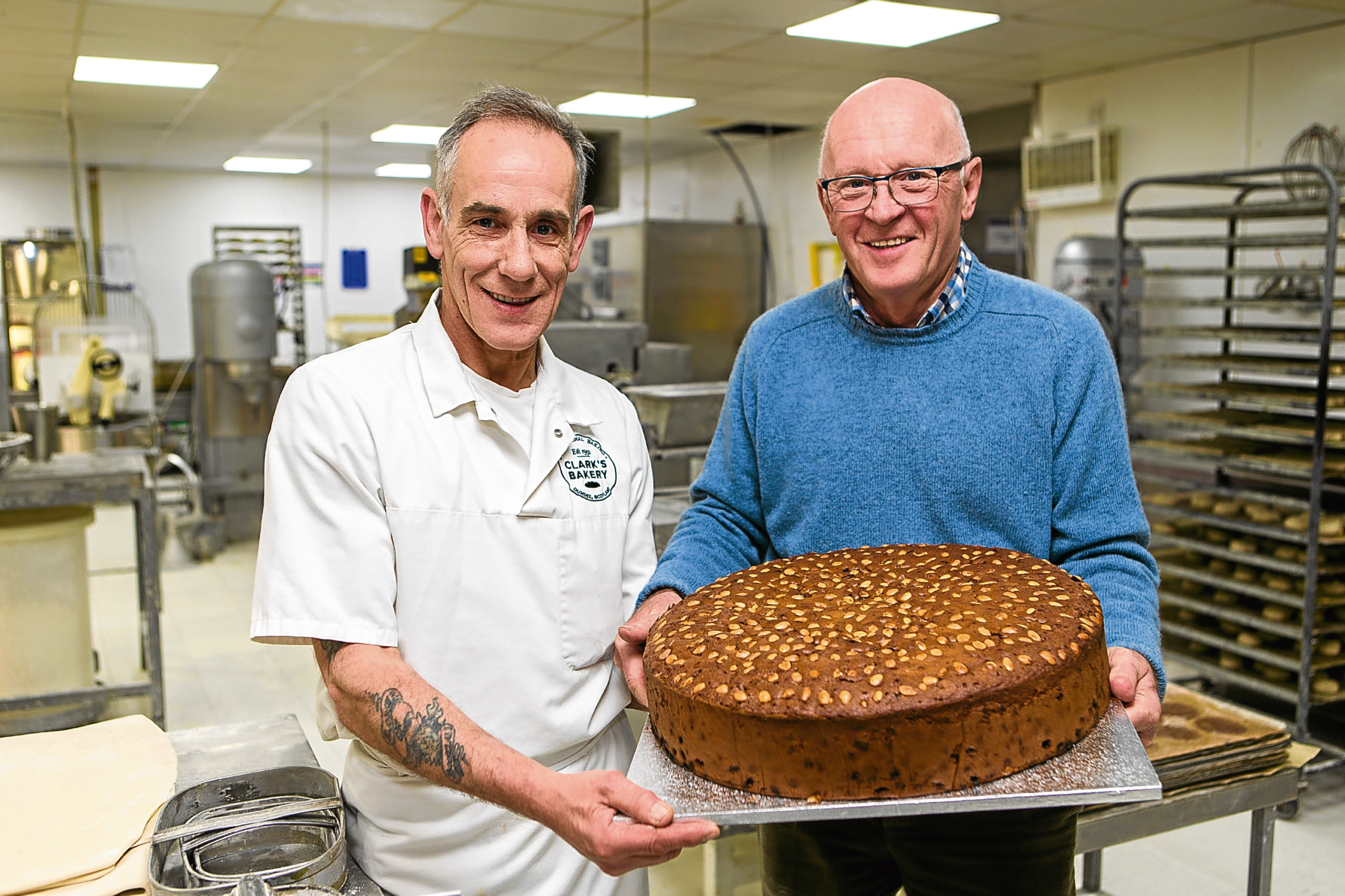 "Baker Colin Smith (left) holds the ""biggest Dundee Cake ever made"" with bakery owner Alan Clark."