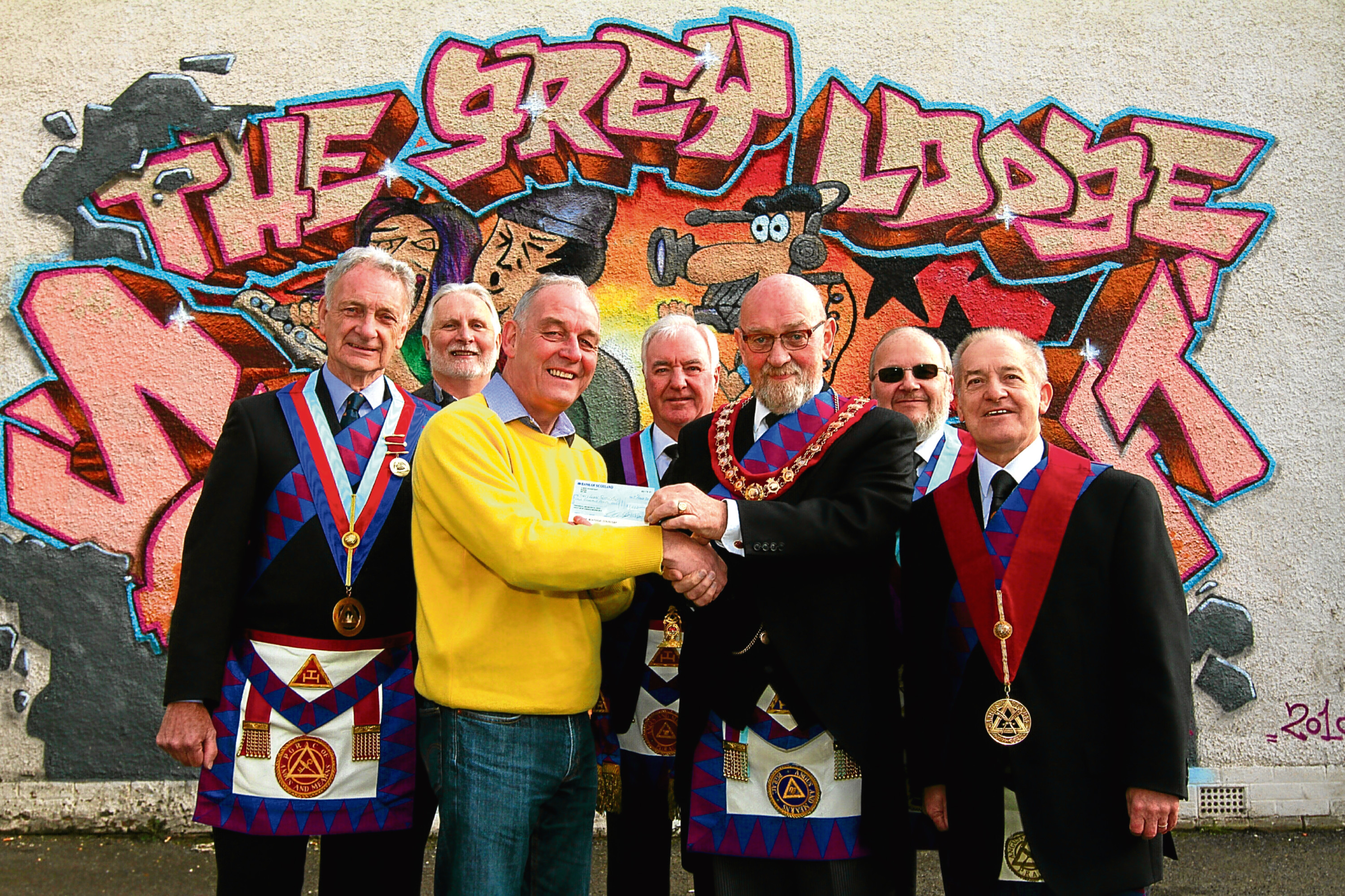 Manager of Grey Lodge, Alan Duncan, (yellow jumper) accepts cheque from Gordon Ross, watched by Andy Stewart, Iain Glass (chairman, Grey Lodge), Eddie Bonnar, Bill Beckers and George Milne (all of Grand Royal Arch Chapter)