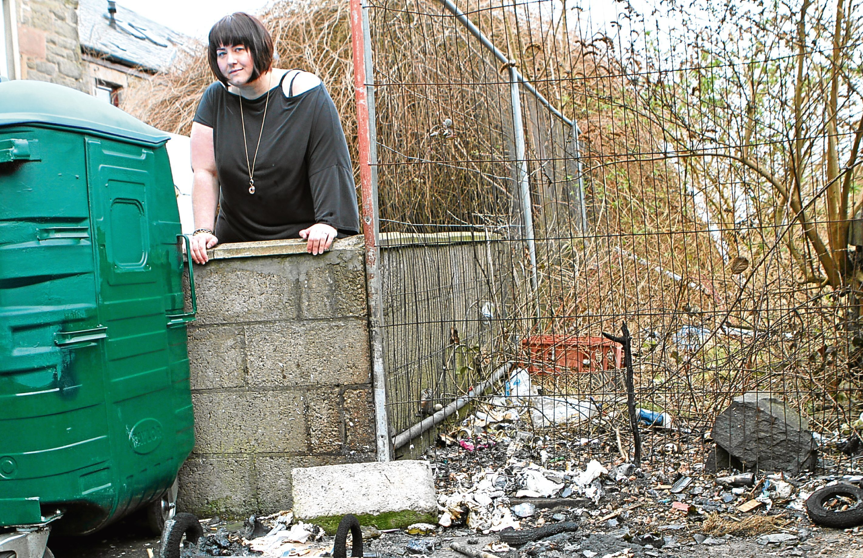 Wendy Sturrock, who owns a business on Dura Street, at the spot where the wheelie bins were set alight