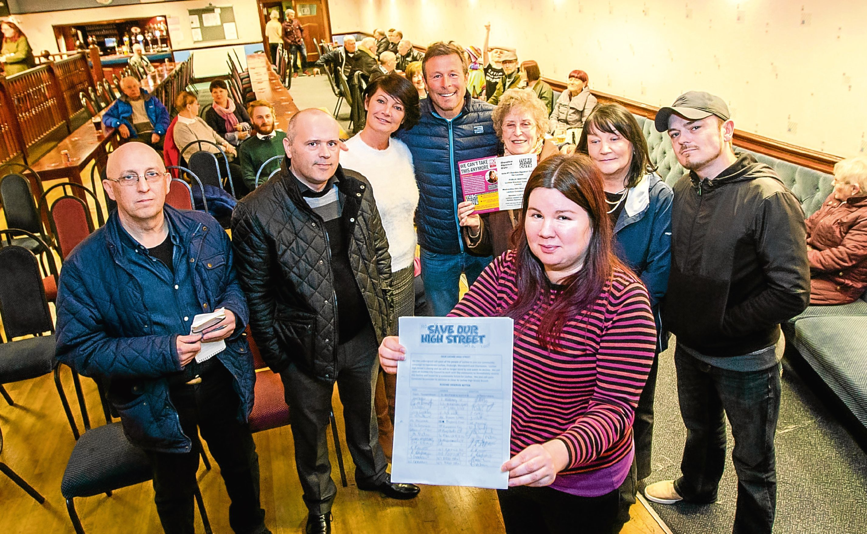 Leah Ganley (organiser, front) holds the signed petition alongside Paul Smith (far left, Lochee trader) next to Ian Mckay (chair of the event)