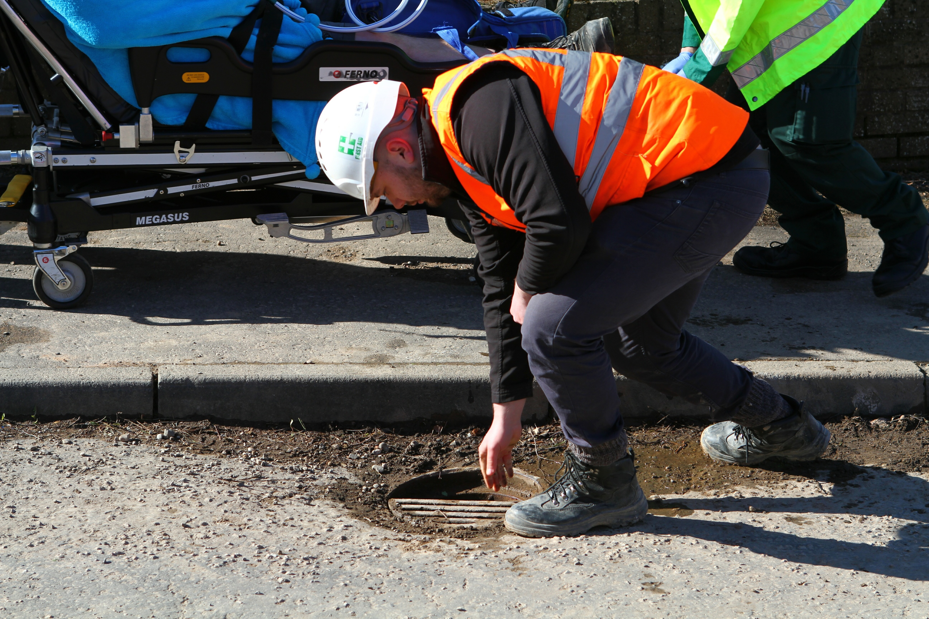 A workman replaces the cover of the drain that Mark Davidson, an employee with Buildbase, fell into