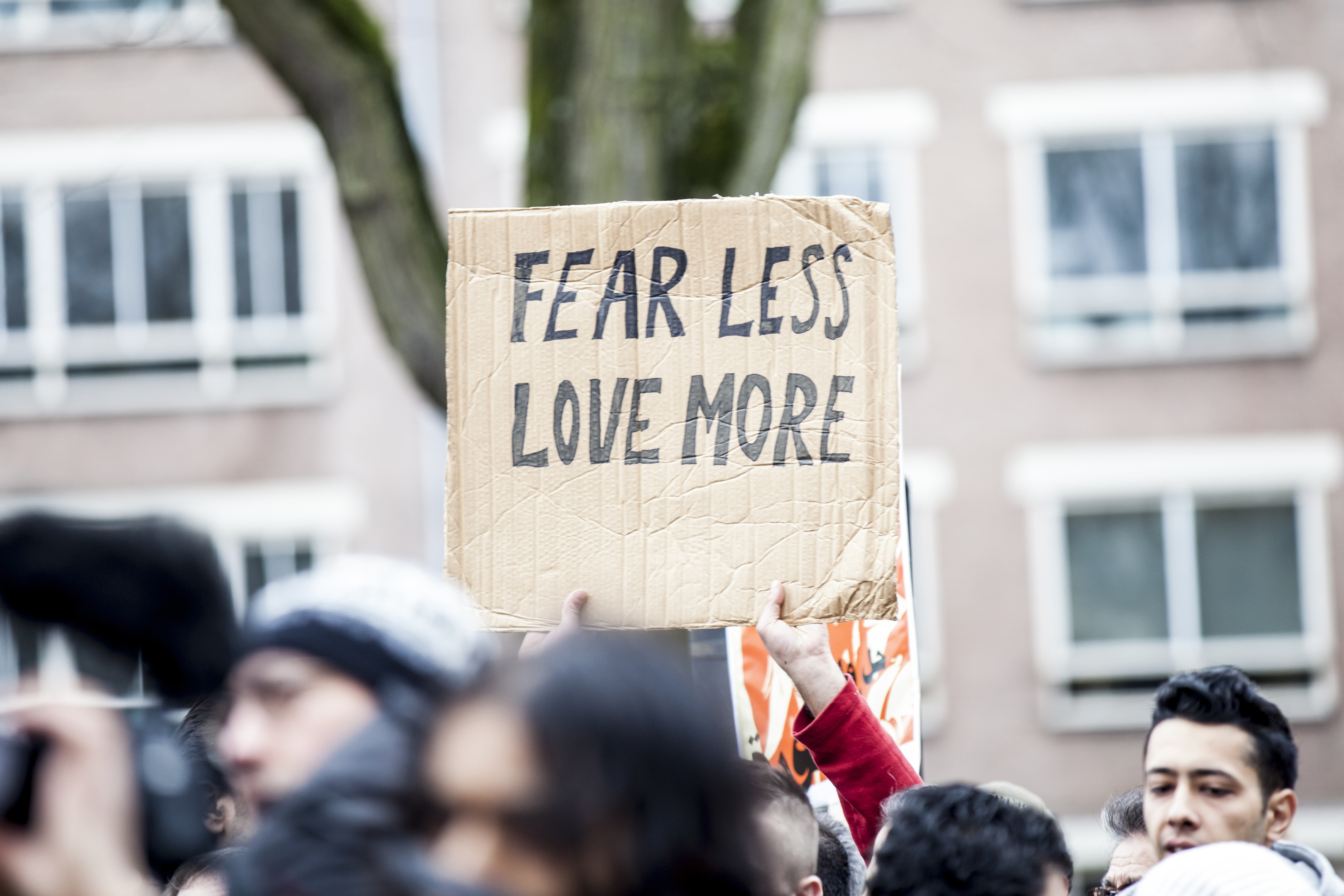 """Amsterdam, The Netherlands - February 6,2016: Crowd of protesters with their flags and banners at the public multi-cultural demonstration organized to protest against racism and islamophobia named """"Refugees welcome, racism not!"""". A sign says: Fear """"less hate, love more"""""""