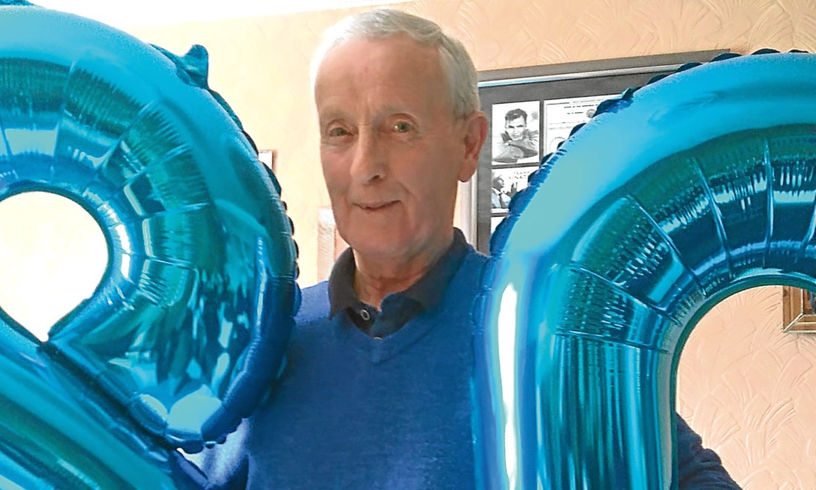 Tam at home with inflatable numbers indicating his age