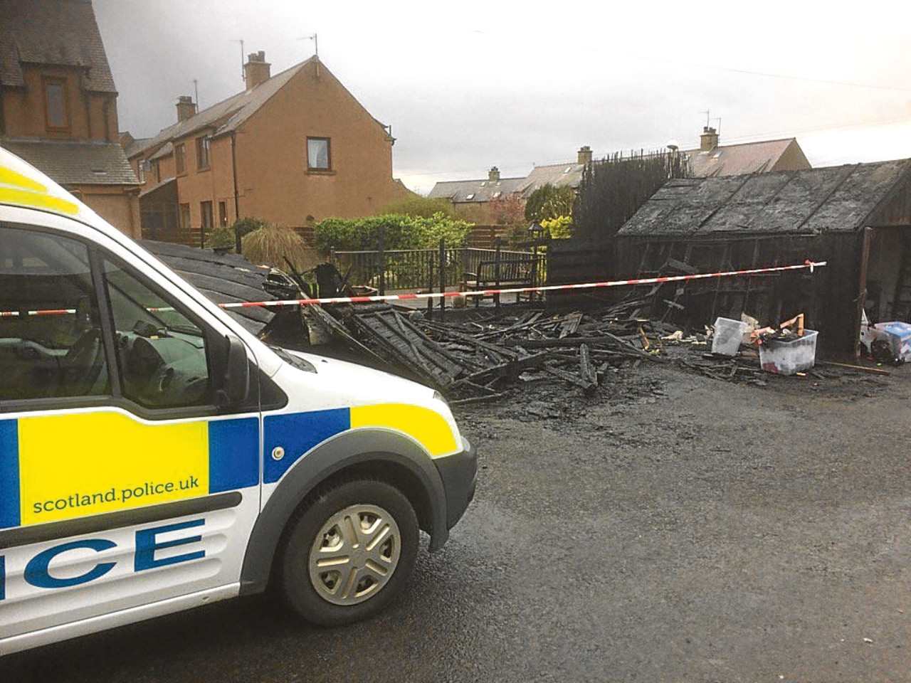 Police at the scene of the garage fire where several properties were left damaged.