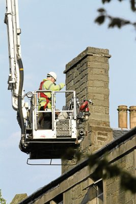 Officers check the chimney of a damaged flat in Park Avenue