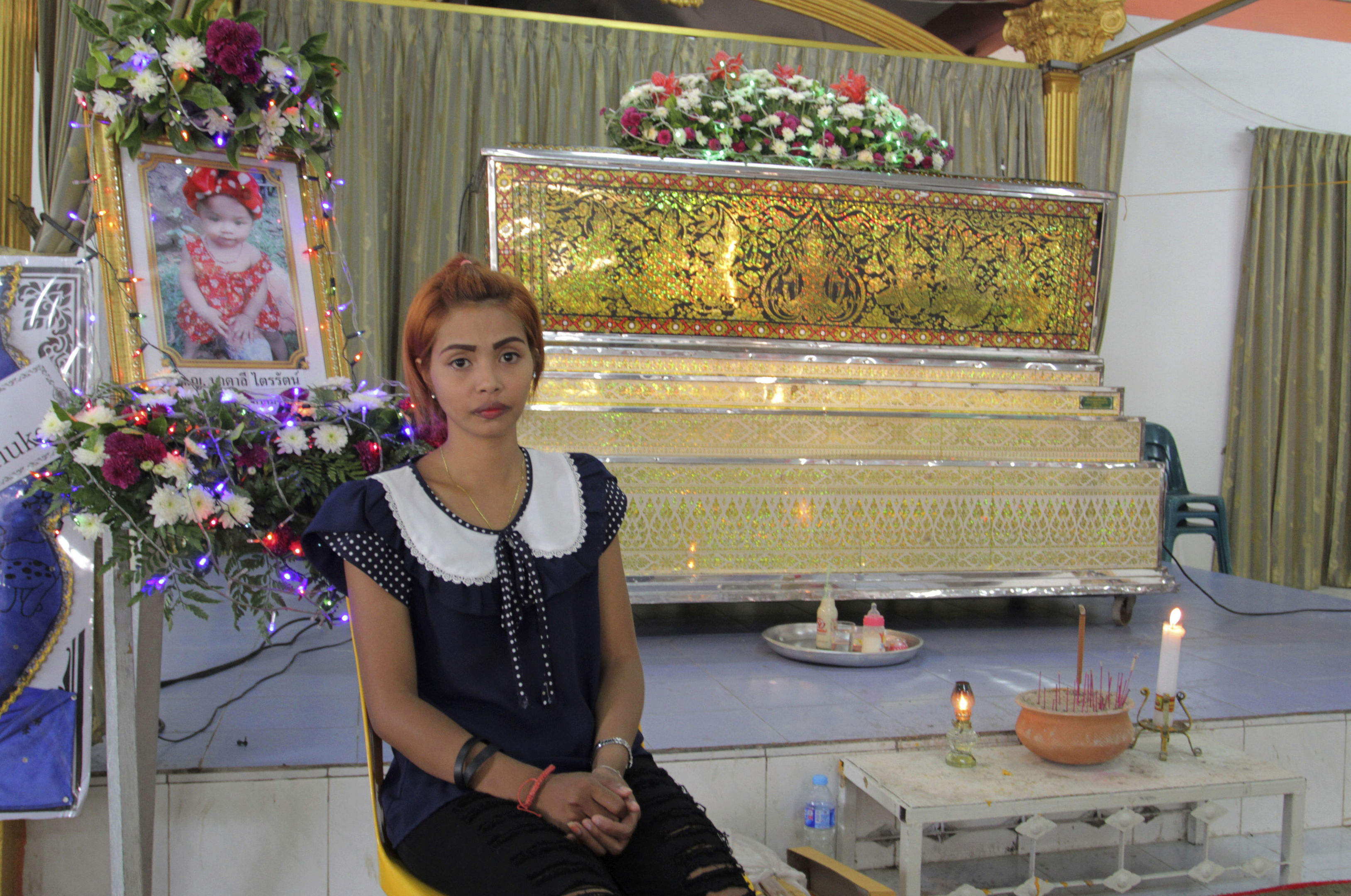 Chiranut Trairat, mother of an 11-month-old baby girl, sits in front of her daughter's coffin