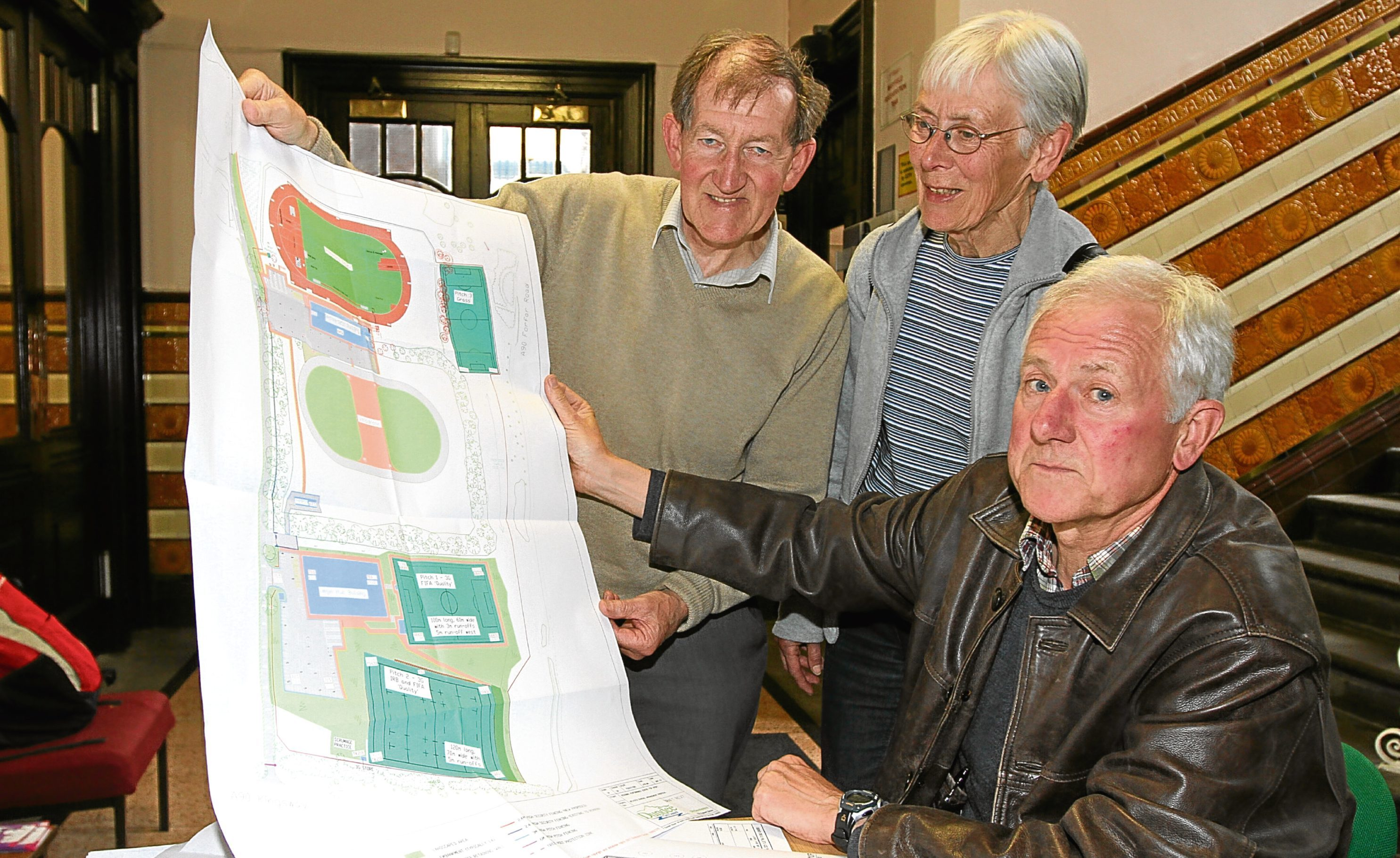 Ron Oliver, Barbara Oliver and Dave Hamilton look at the new plans for the Caird Park sports complex.