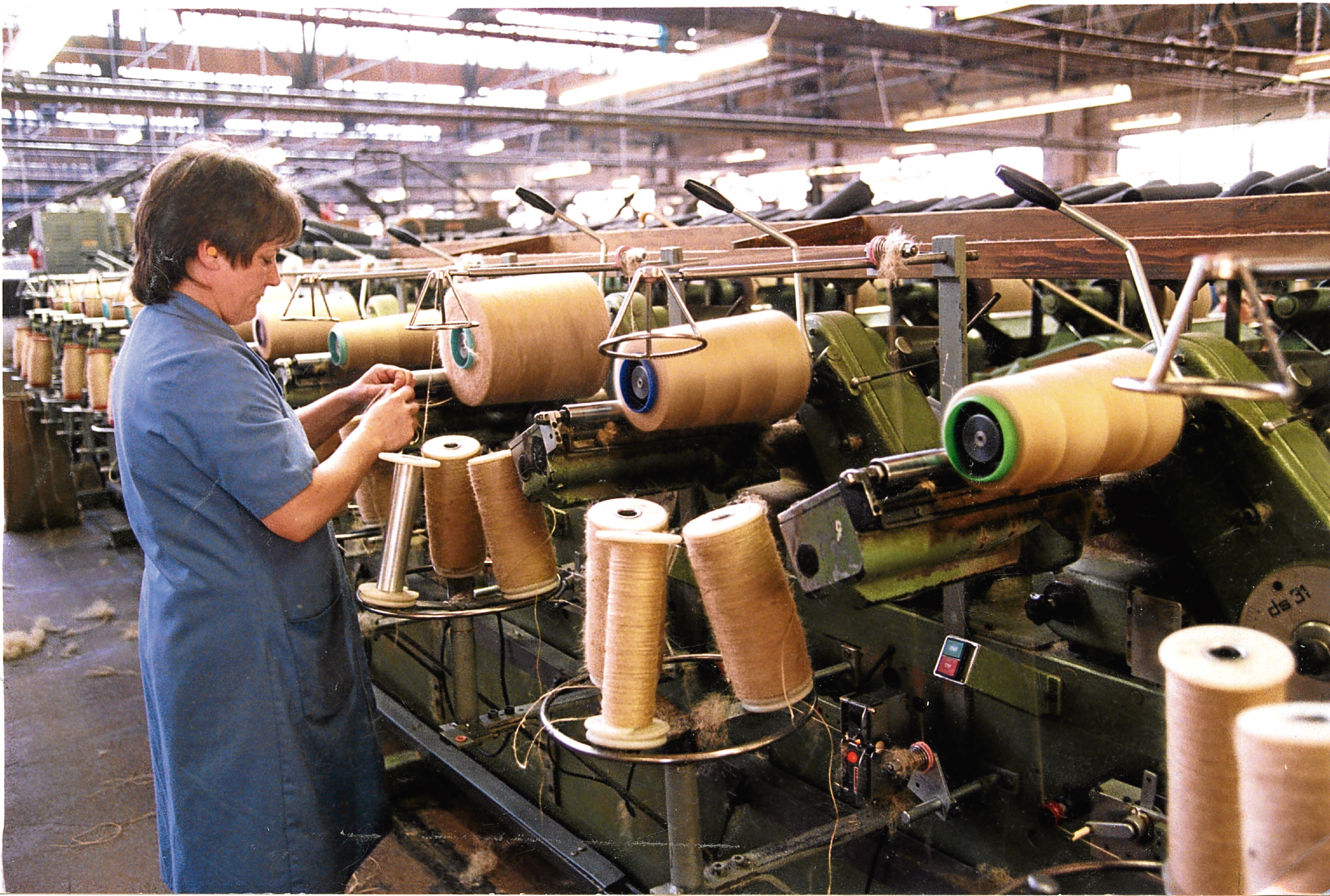 A lone worker tends to a vast bank of machines and an assorted array of jute reels at the former Tay Spinners factory in Dundee in 1998.