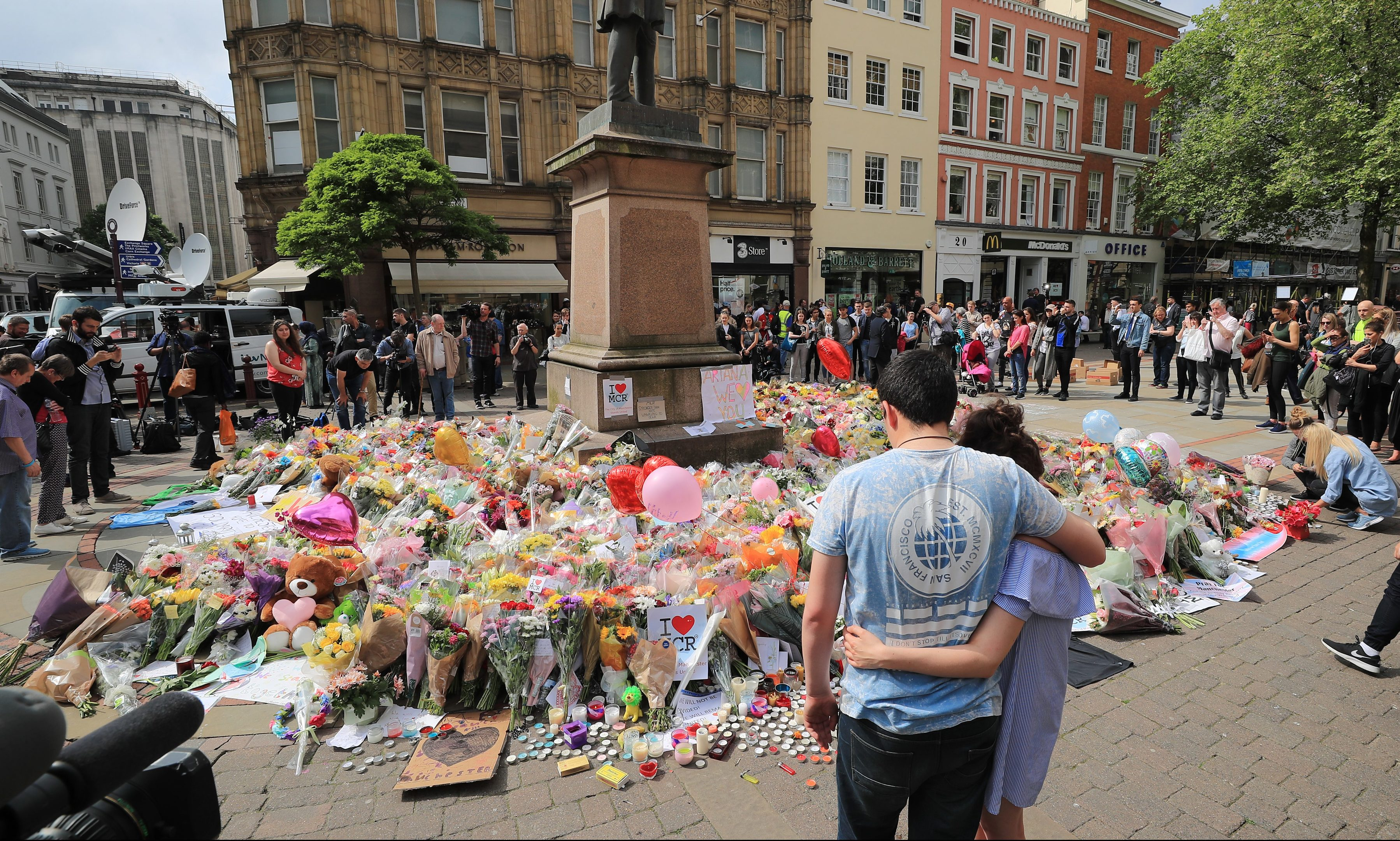 People look at flowers in St. Ann's Square, close to the Manchester Arena where a suicide bomber killed 22 people