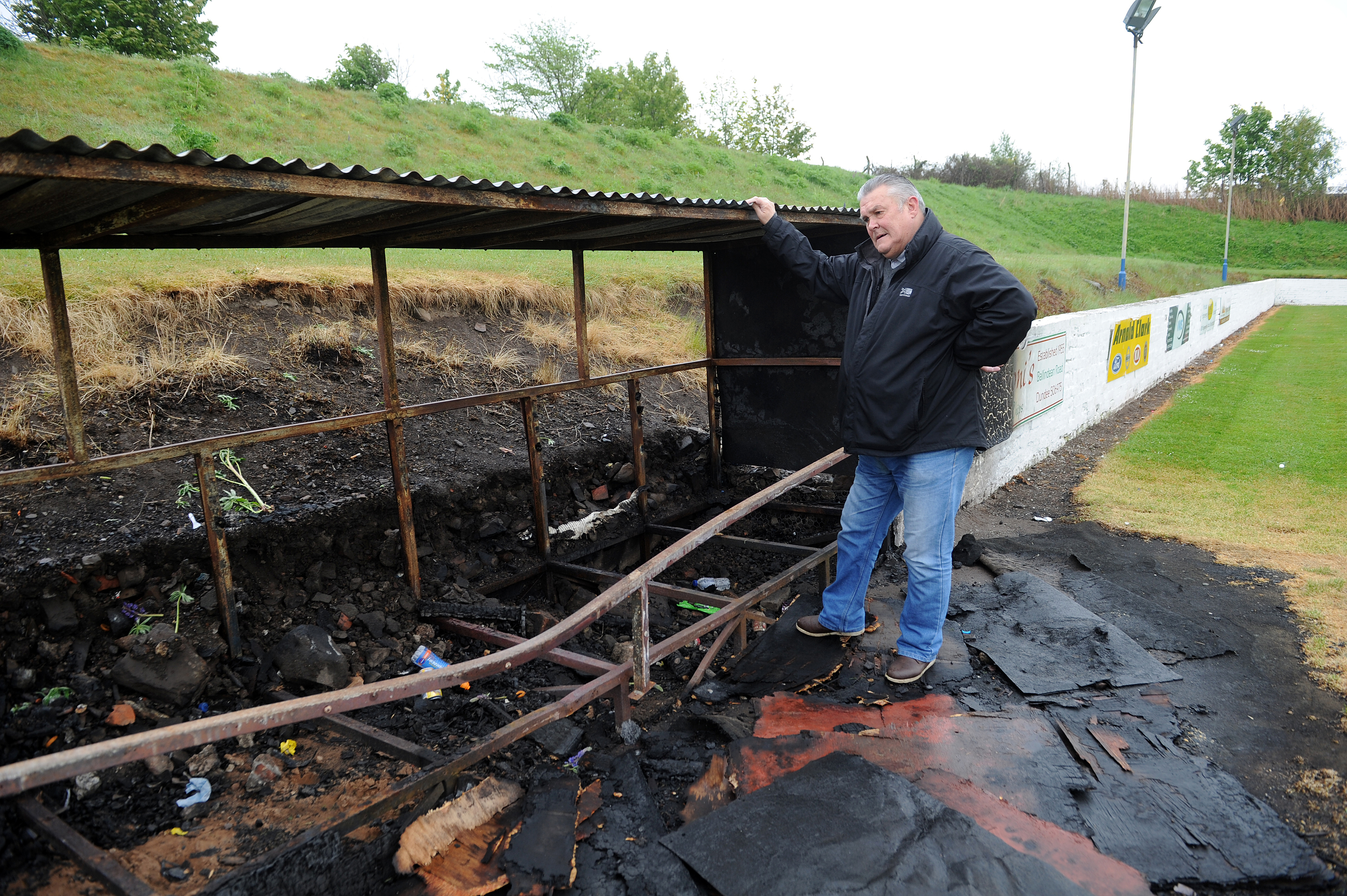 Club secretary Brian Coutts next to the fire-damaged dugout.