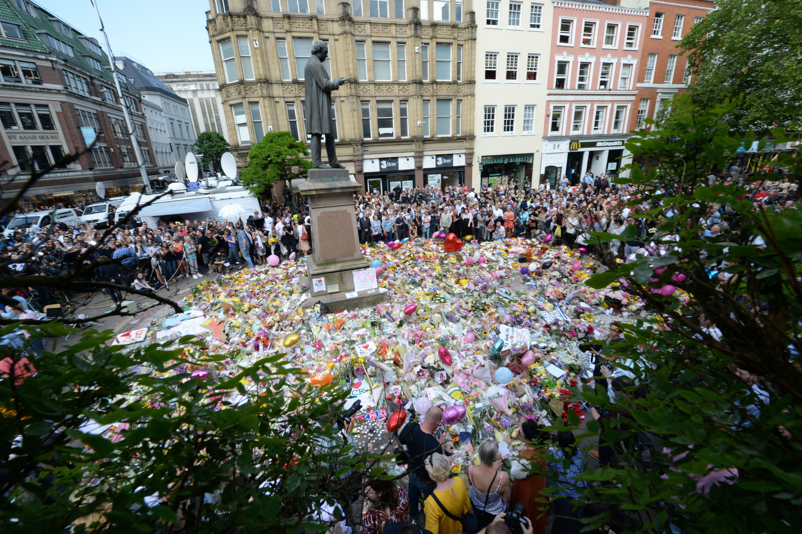Crowds gather to pay their respects at the floral tributes in St Ann's Square, Manchester