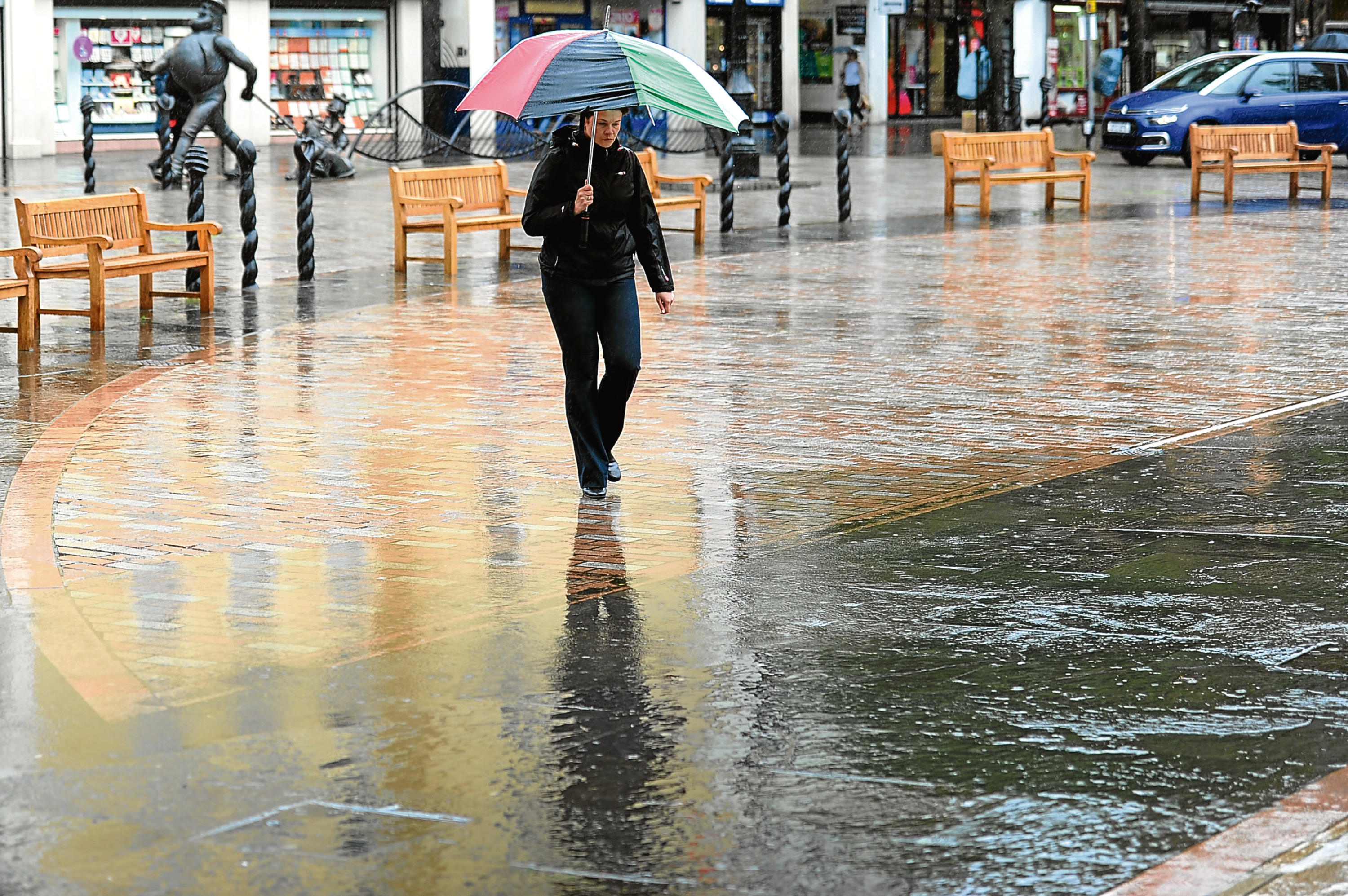 A member of the public braves a heavy downpour in Dundee High Street.
