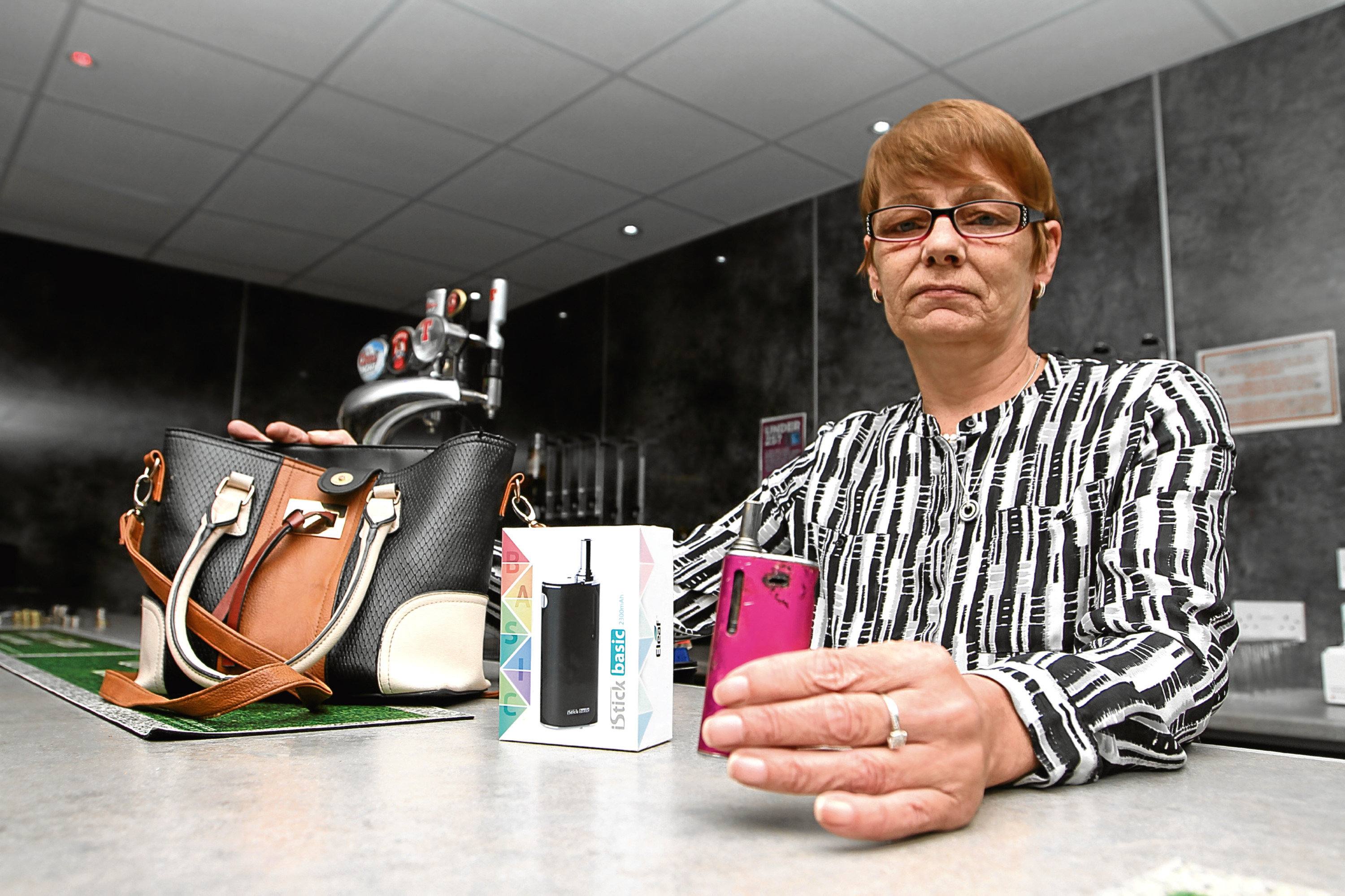 Laura White, manageress of Douglas Sports Club, with her handbag and the e-cigarette lighter.