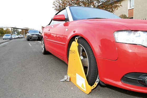 A car clamped after action by tax enforcers. The clamps are only removed if the owner pays a fine.