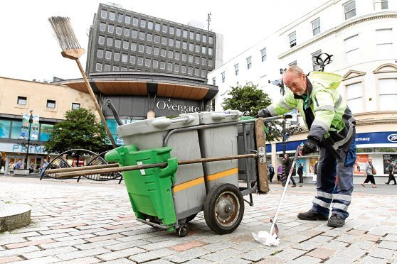 Dundee City Council street cleaner Douglas Robbie picks up rubbish.
