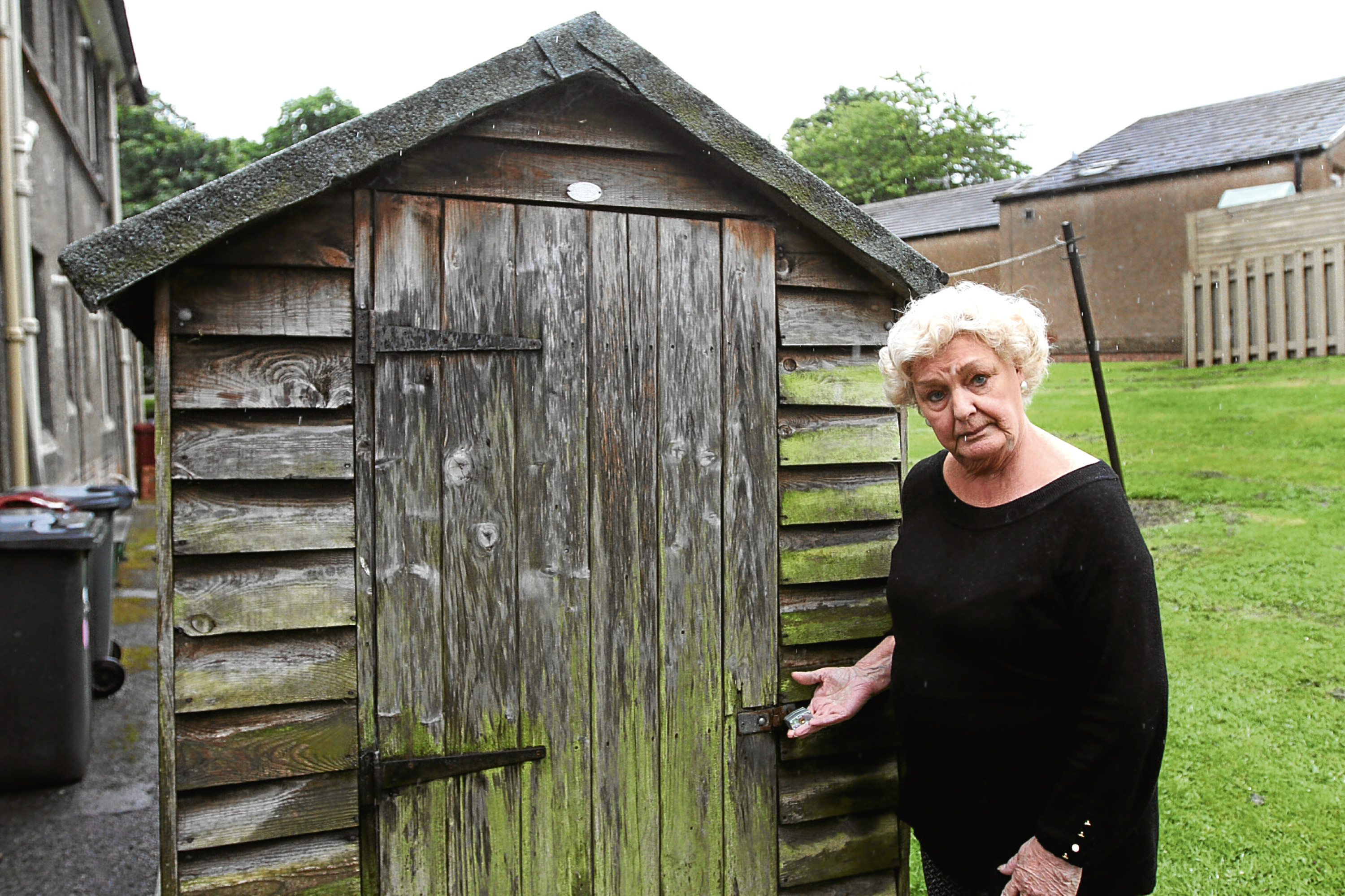 Margaret Barry is pictured next to her shed, which was being emptied by three men when she came home one day.
