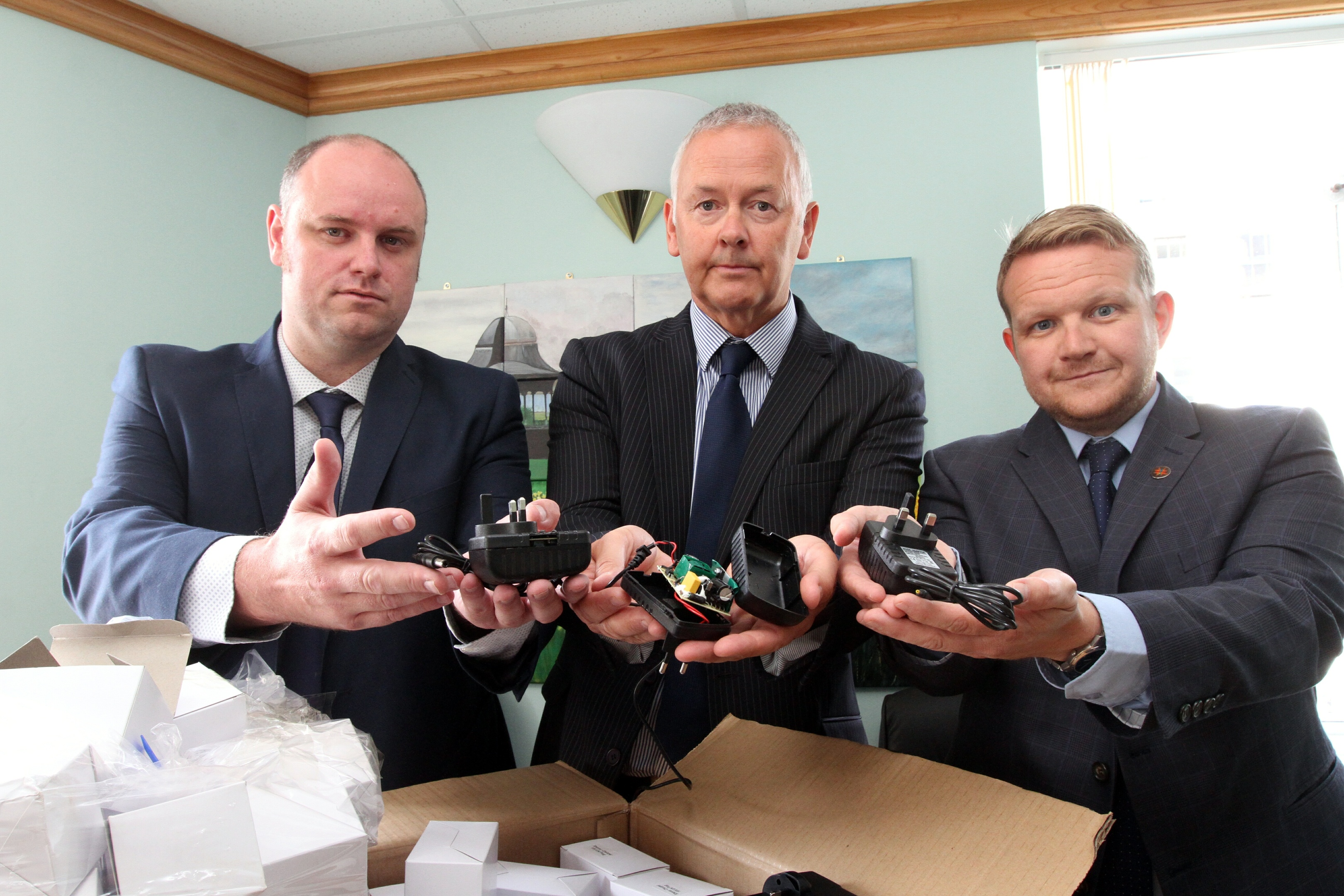 Stuart Houston and Raymond Lynch of Trading Standards and Cllr Alan Ross with some of the chargers.