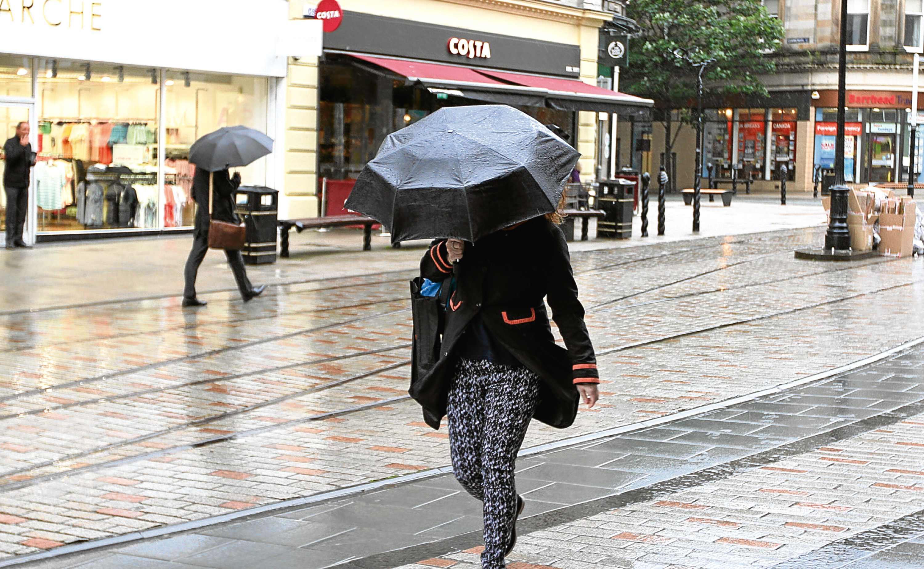 A woman battles the rain during the second-wettest June since 1910.