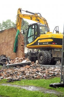 Workers from Dundee Plant in a digger knocking down the ruined building and clearing rubble